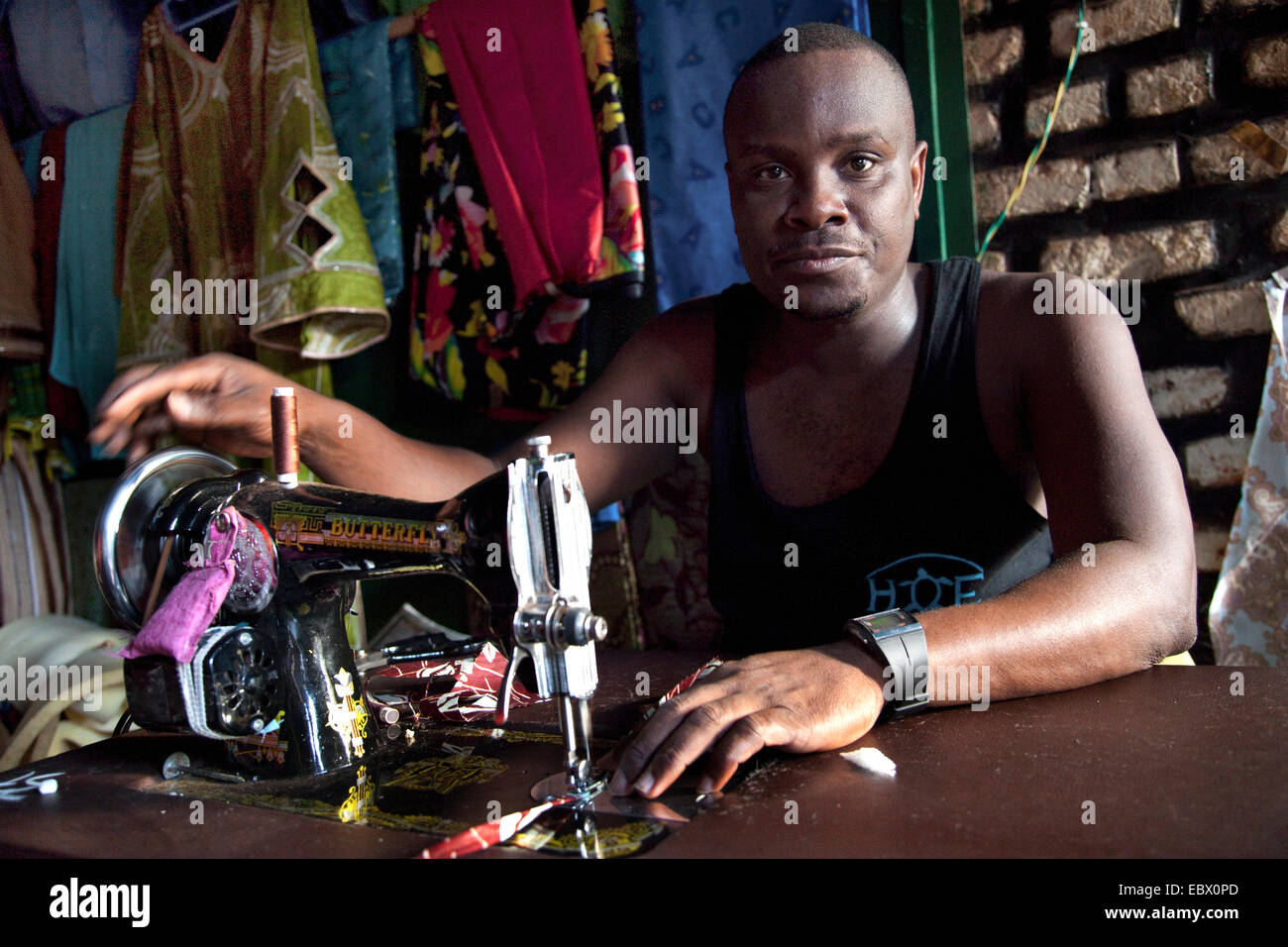 Tailer sitting at the sewing machine in his atelier, finished clothes in the background, Rwanda, Nyamirambo, Kigali Stock Photo