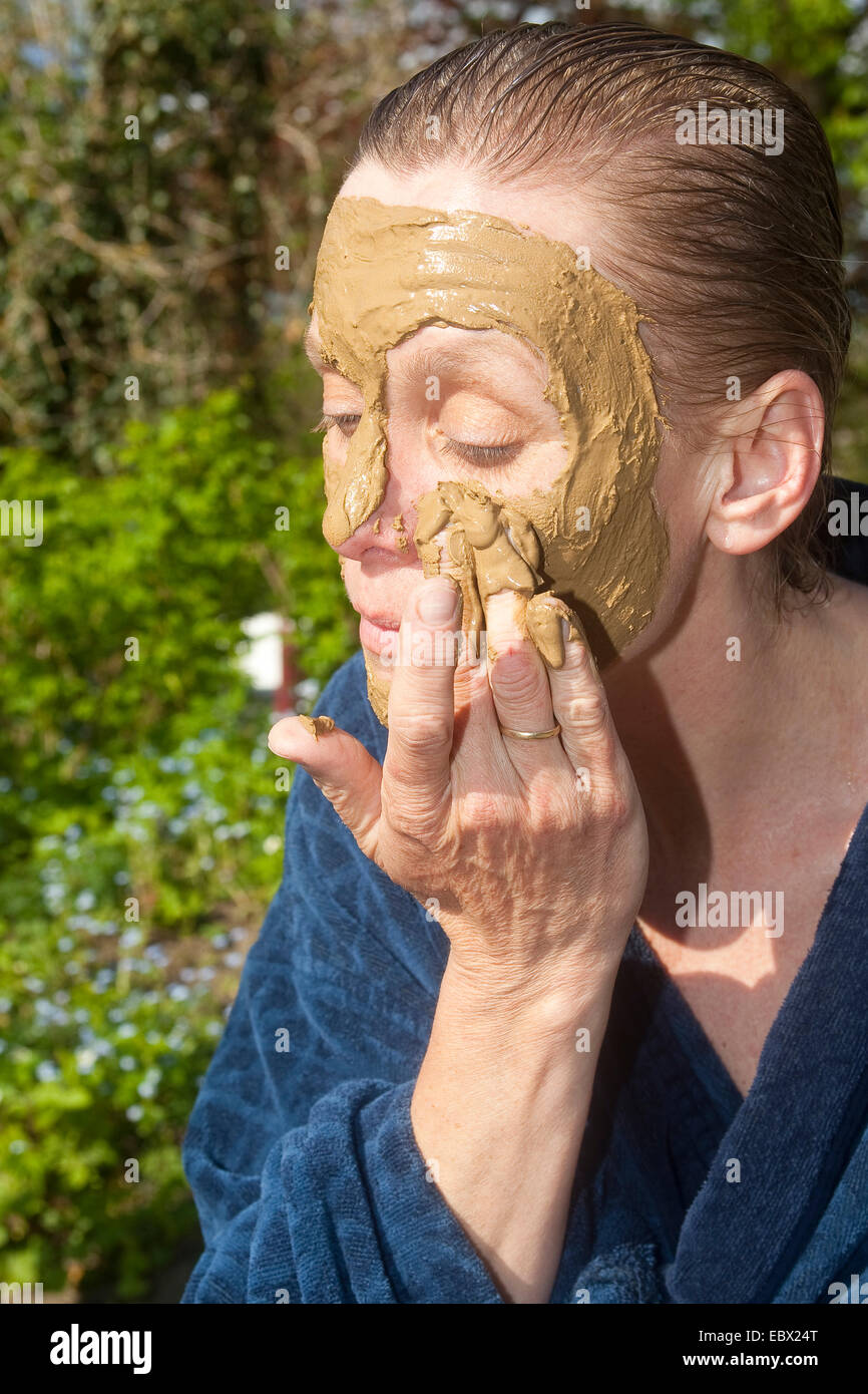 woman putting healing earth onto her face - Stock Image