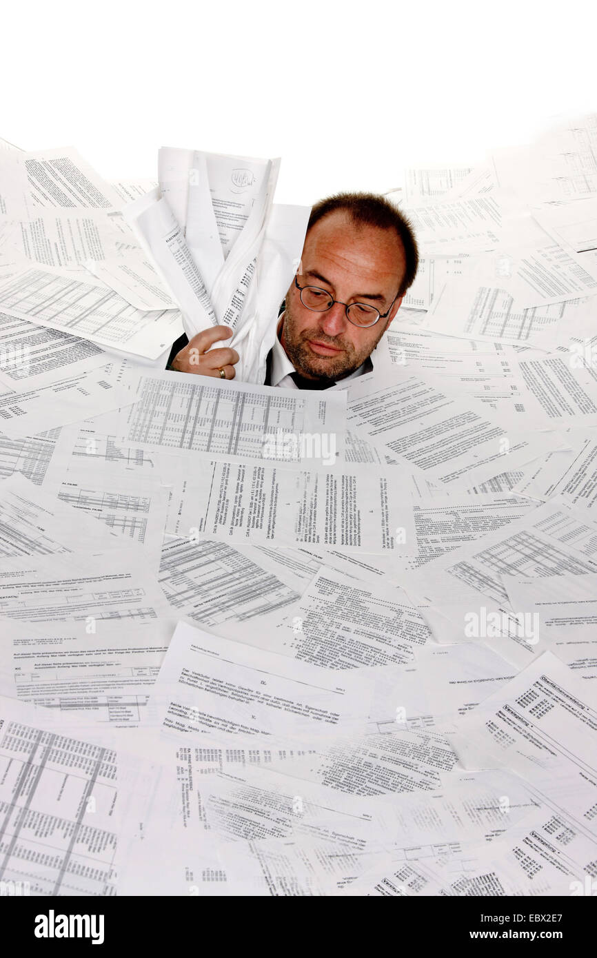 business man bogging in a heap of text documents to the neck - Stock Image