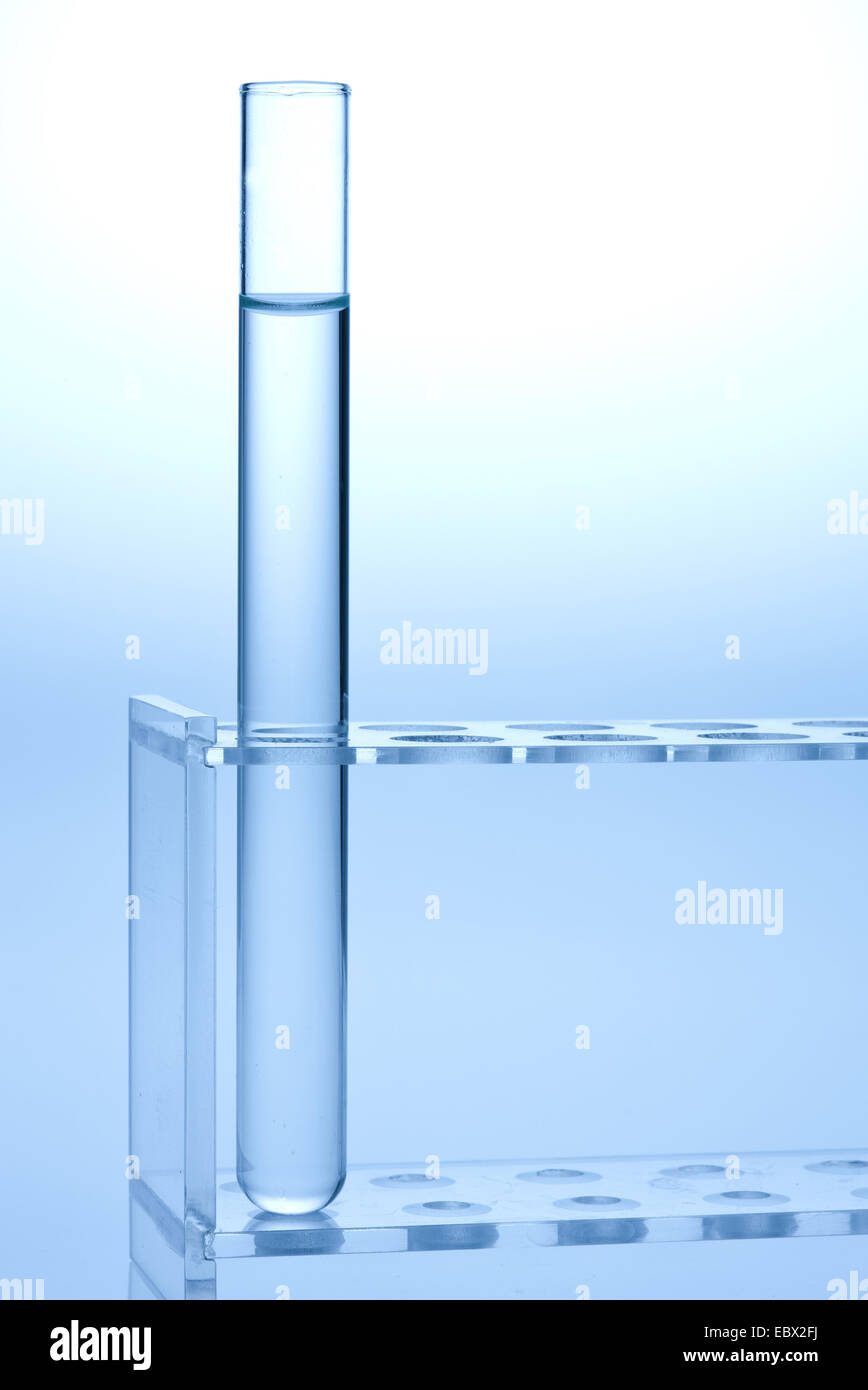 single test tube filled with colourless liquid standing in a test tube rack - Stock Image