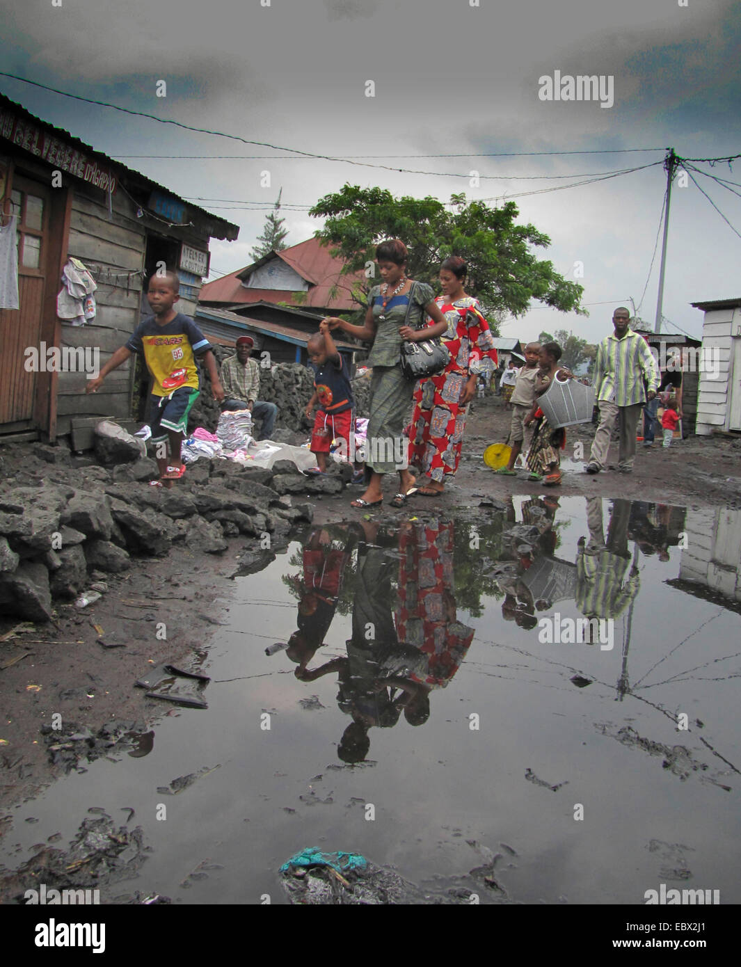 pedestrians walking on lava stones at the edge of big puddles after heavy rain in the rainy season, Republic of Stock Photo