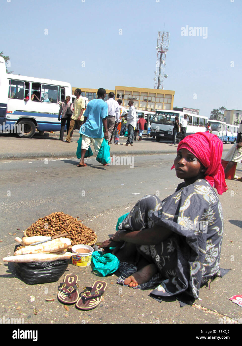 street scene in the capital city; young woman on the ground selling cassava and peanuts to passengers at the central bus station near the market, Burundi, Bujumbura marie, Bujumbura Stock Photo