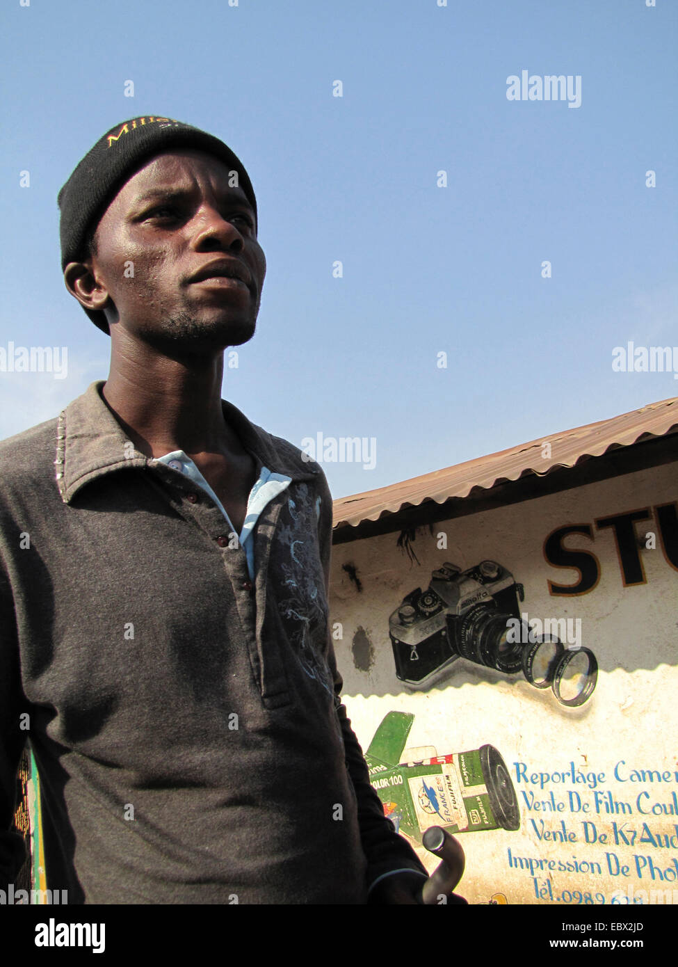 young man with cap in front of photo studio, Burundi, Bujumbura marie, Bwiza, Bujumbura - Stock Image