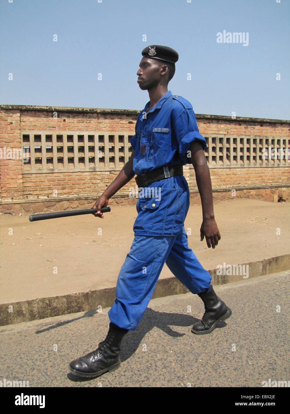 police officer with baton patrolling on a large street of the capital city, Burundi, Bujumbura marie, Rohero 1, - Stock Image