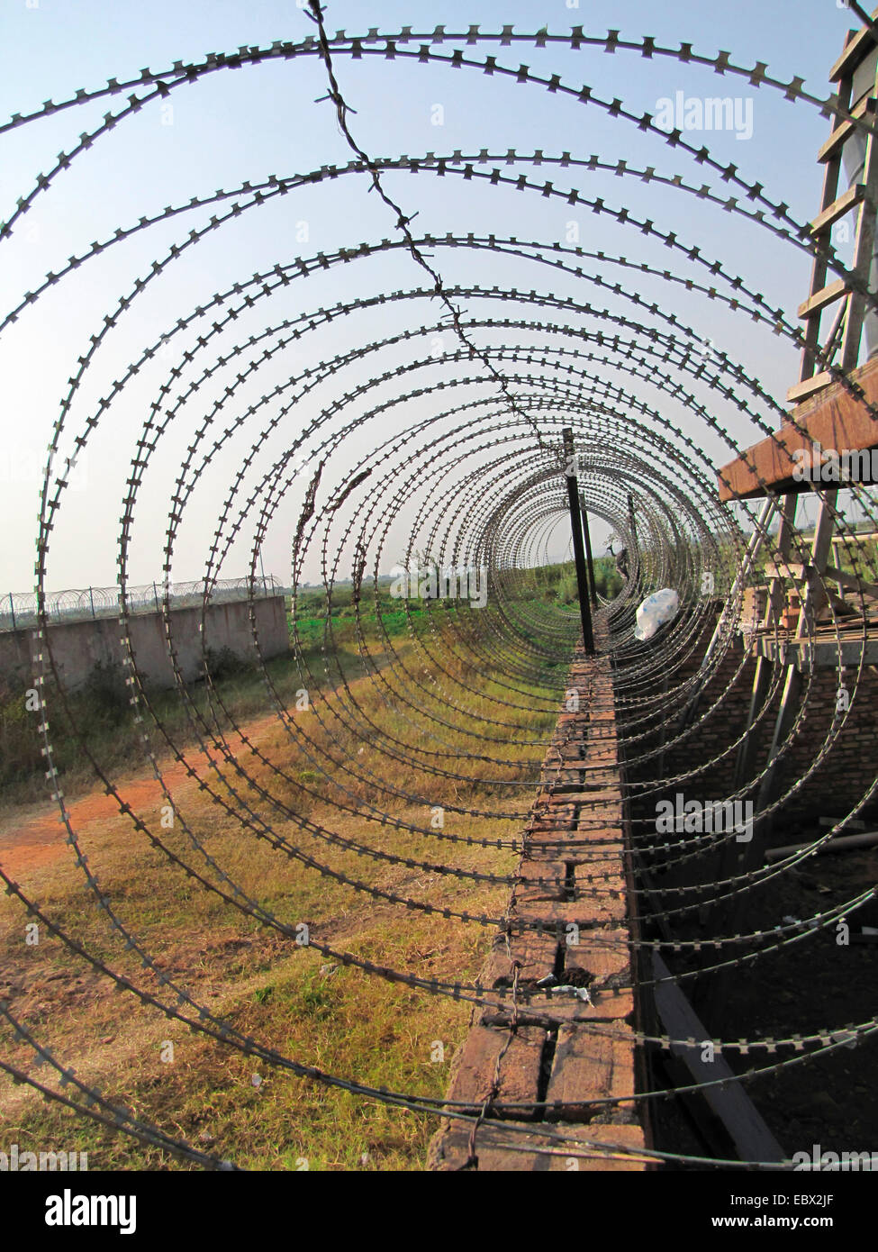 barb wire on a wall securing a compound, Burundi, Bujumbura marie, Cartier industriel, Bujumbura Stock Photo