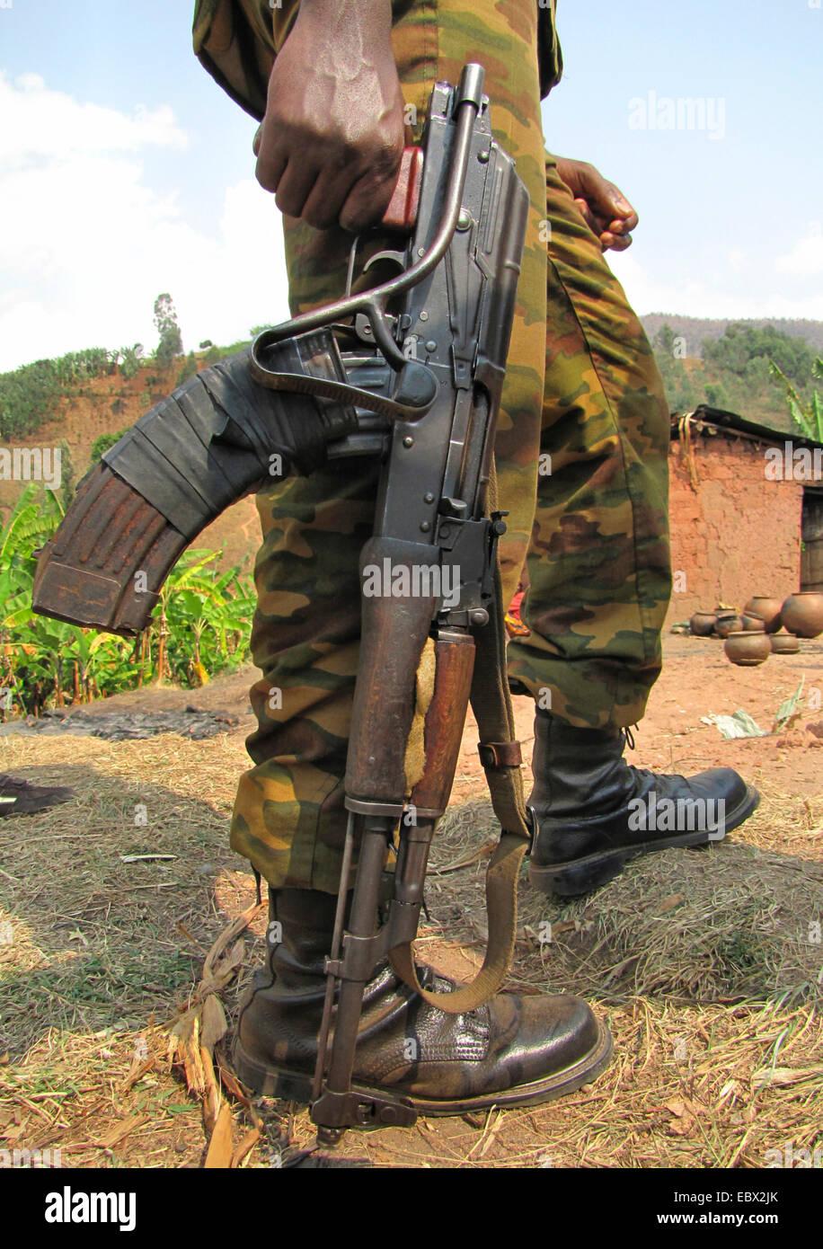 legs of a soldier with gun standing in front of a mud house, Burundi, Bujumbura rural, Mutimbuzi - Stock Image
