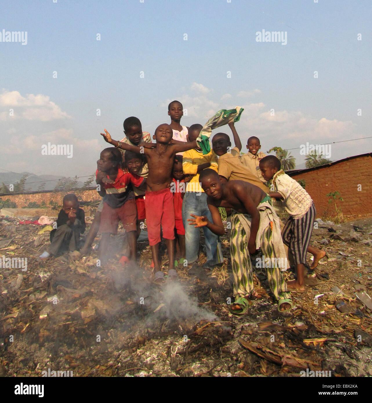 kids posing on a waste dump at the slums behind burning garbage, Burundi, Bujumbura mairie, Buyenzi, Bujumbura - Stock Image