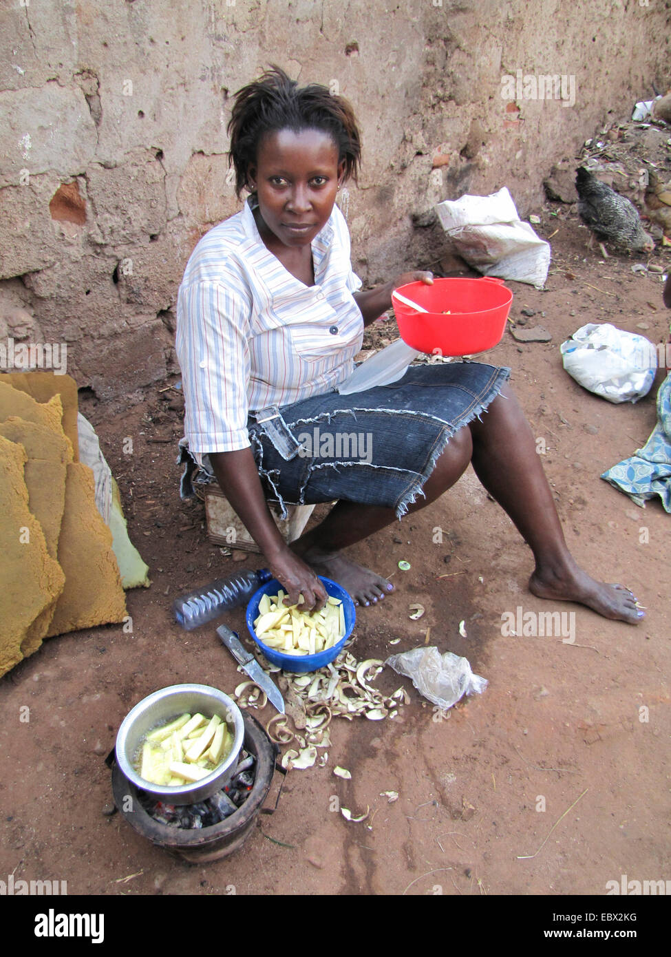 woman is frying potato chips on the soil ground of a backyard, Burundi, Bujumbura mairie, Bwiza, Bujumbura - Stock Image