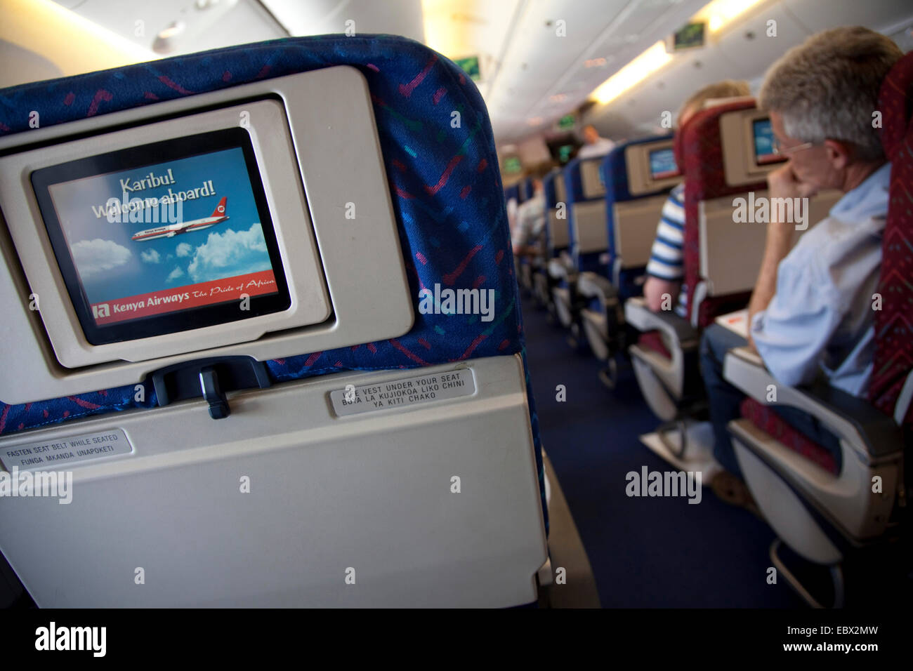 row of seats and passengers in an airplane, Kenya, Nairobi - Stock Image