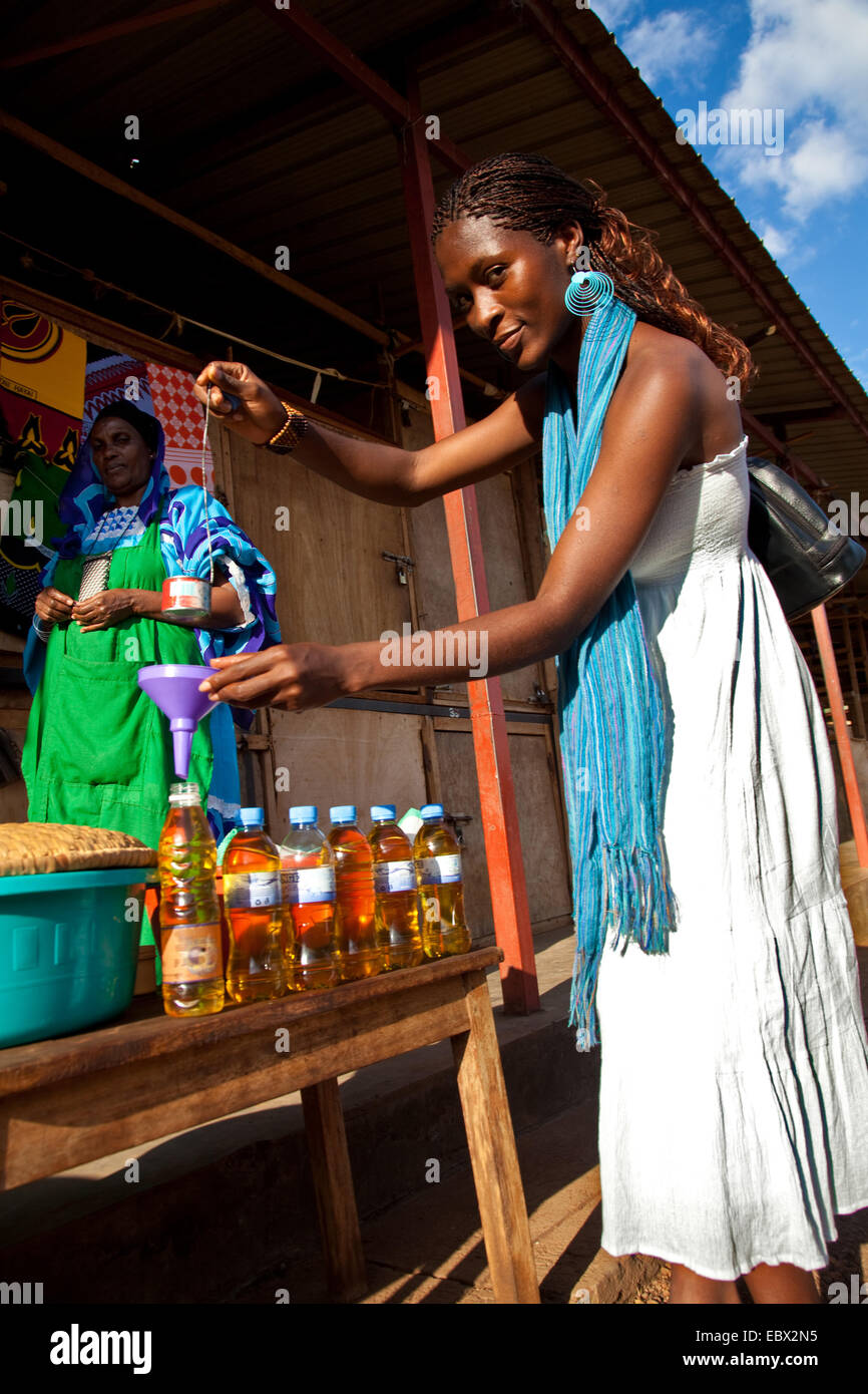 young woman bottling cooking oil on the market, Rwanda, Nyamirambo, Kigali - Stock Image