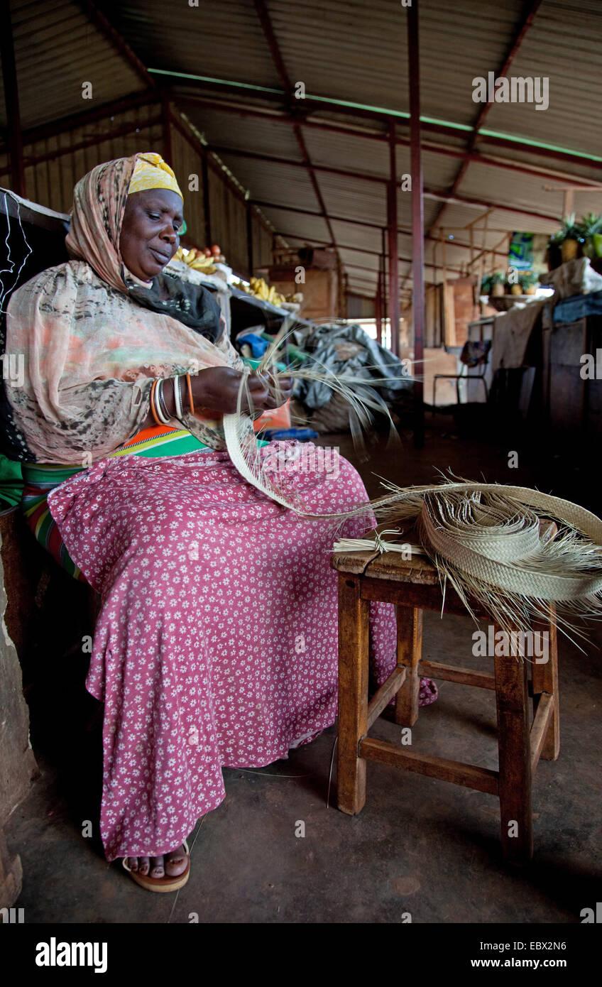 woman braiding basket on a market, Rwanda, Nyamirambo, Kigali - Stock Image