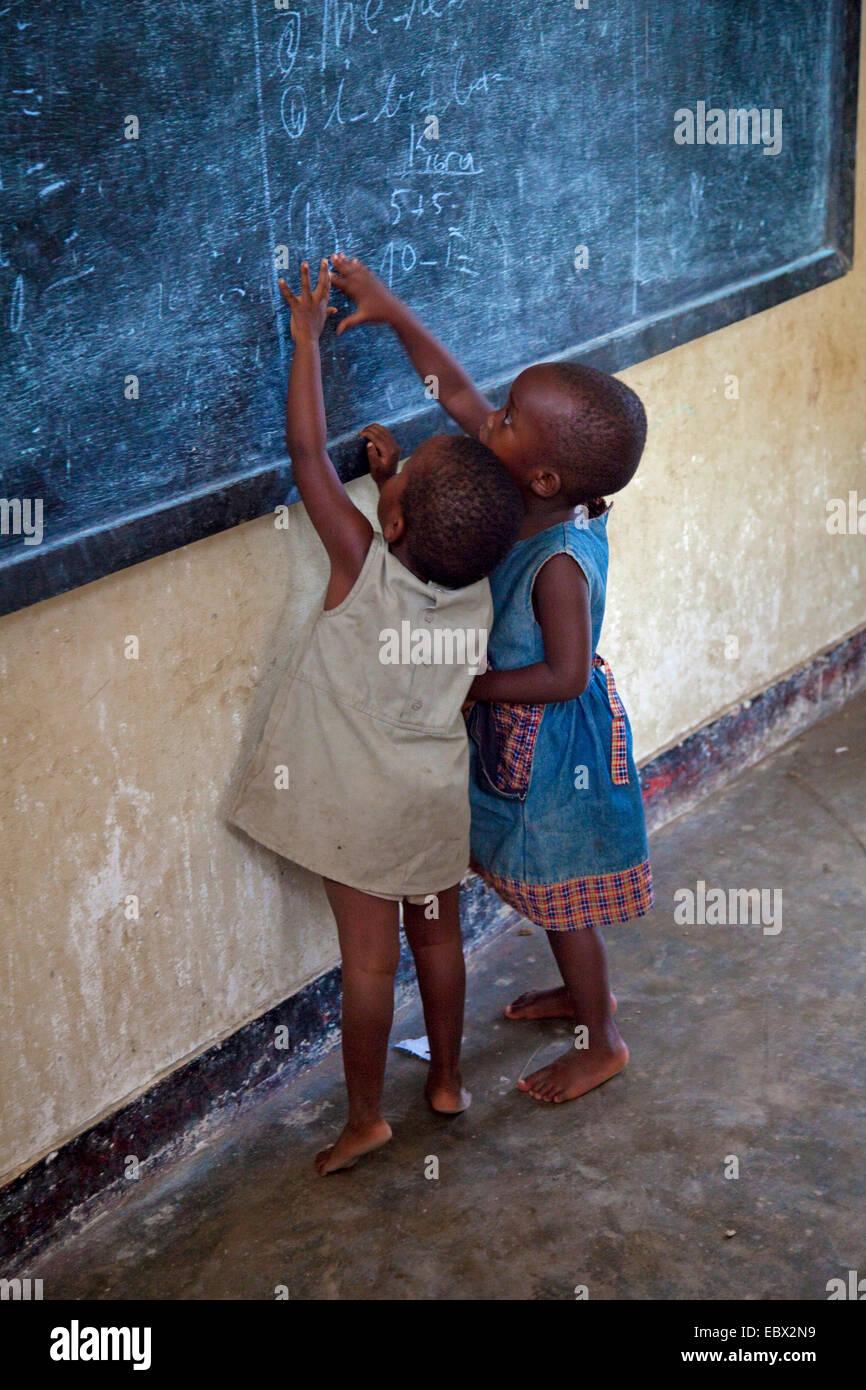two little girls drawing on blackboard, Burundi, Bujumbura Mairie, Bujumbura - Stock Image
