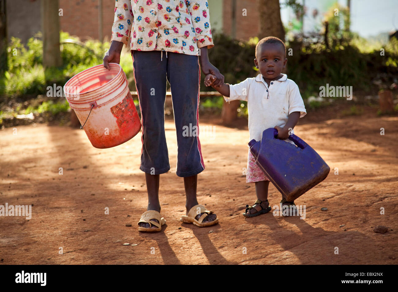 little boy with water can bringing water, Burundi, Makamba - Stock Image
