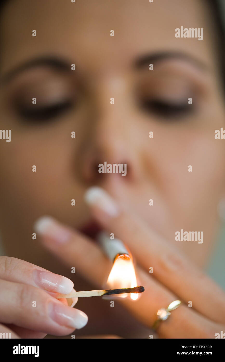 woman lightening a cigarette - Stock Image