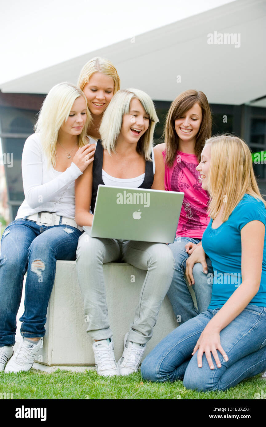 five young girls gathered around a laptop looking at the screen with a smile - Stock Image