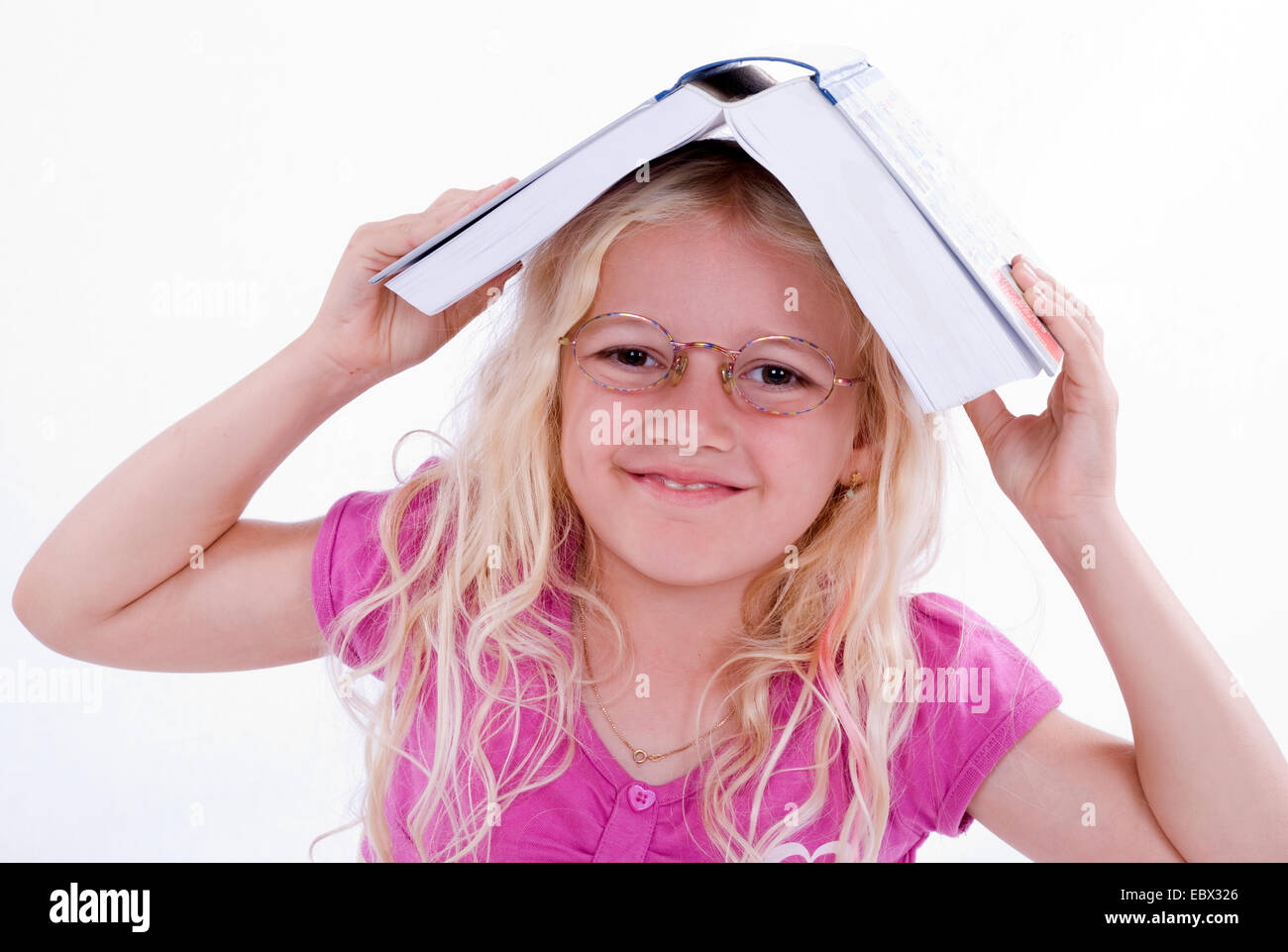 girl with book on her head Stock Photo