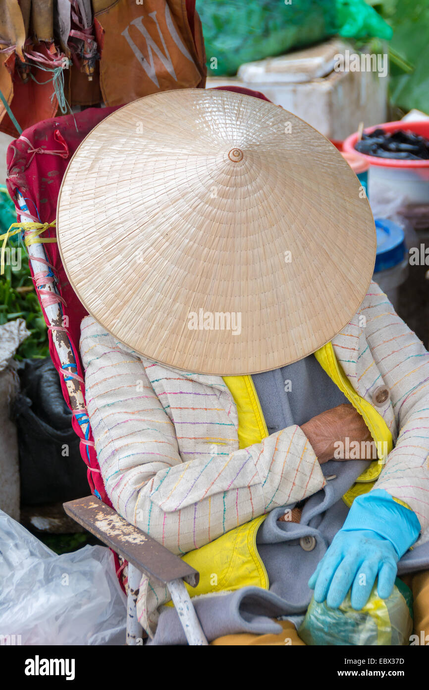 Sleeping female market trader at a local market in Vietnam - Stock Image