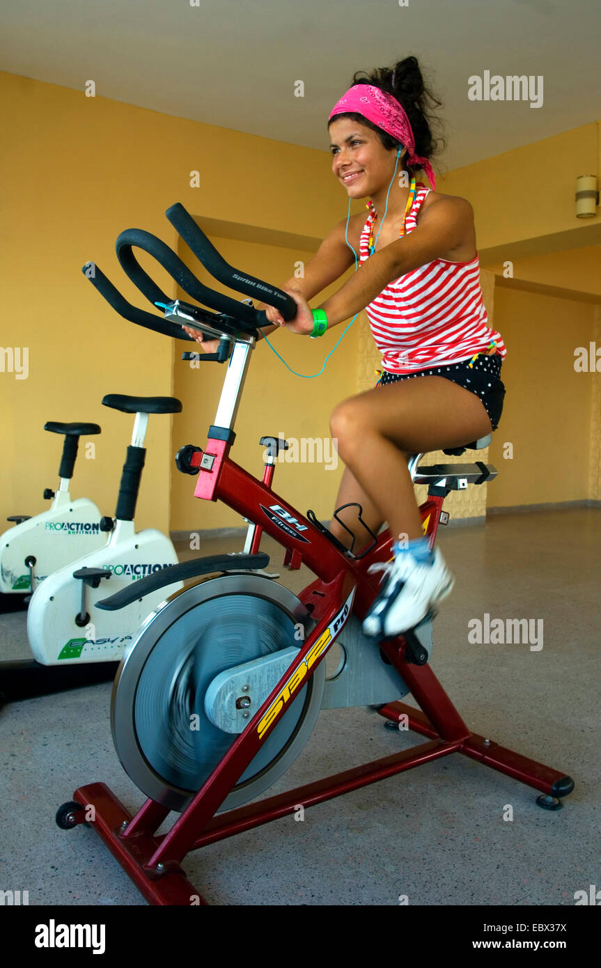 young woman sitting on an exercise machine at the fitness center - Stock Image