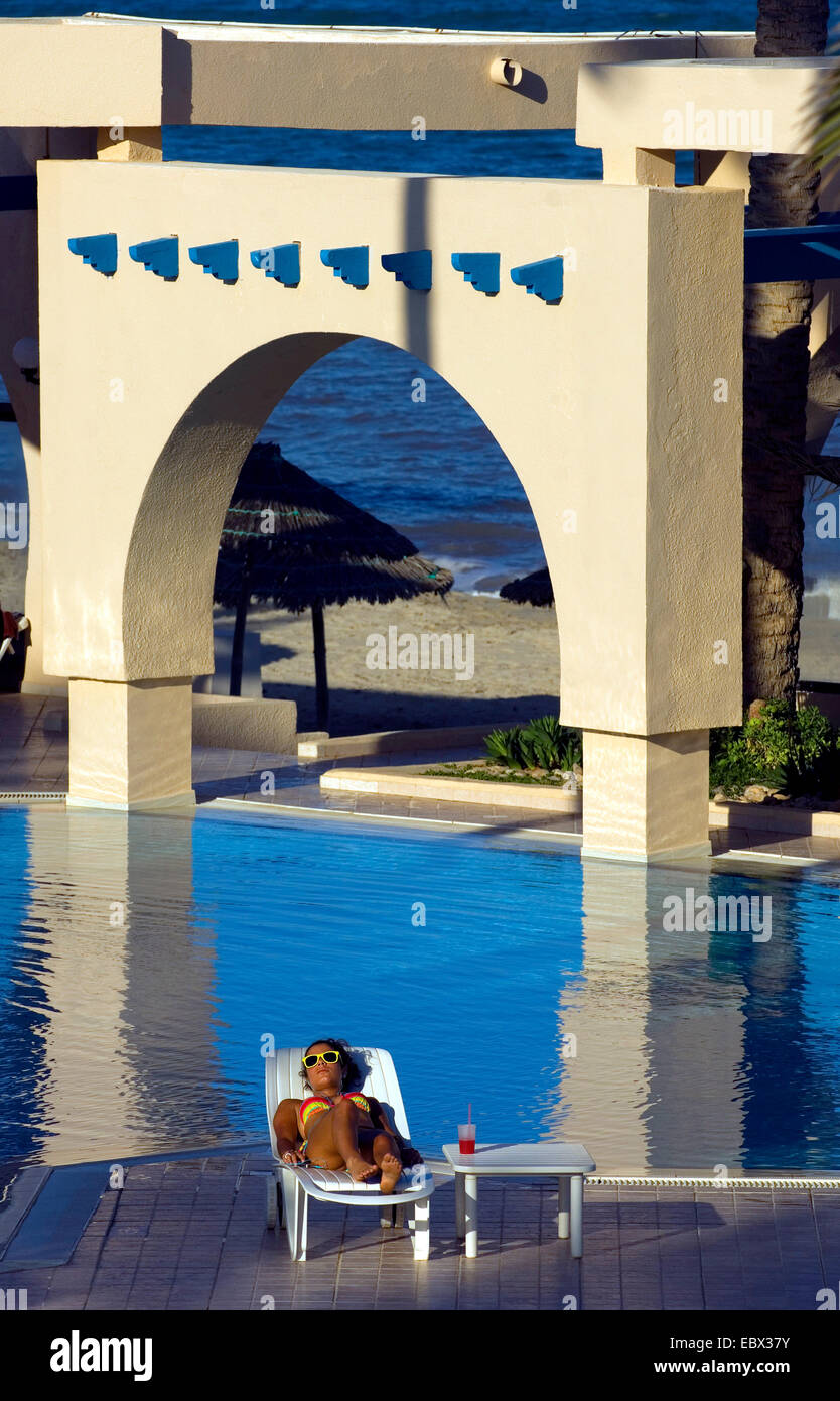young woman taking a sunbath at the swiming pool of a luxurious hotel, Tunisia, Djerba - Stock Image