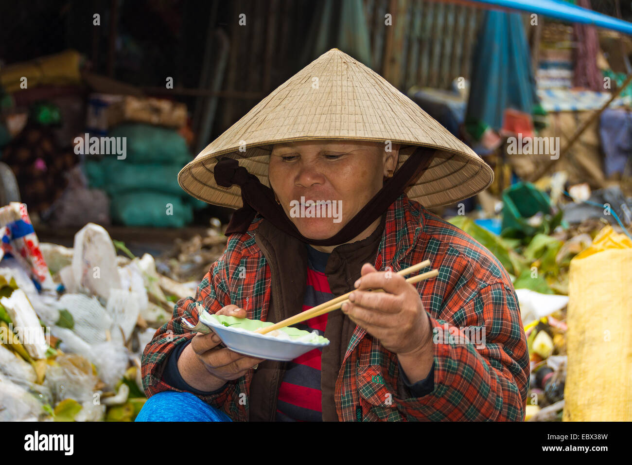 Vietnamese lady market trader eating a bowl of noodles - Stock Image