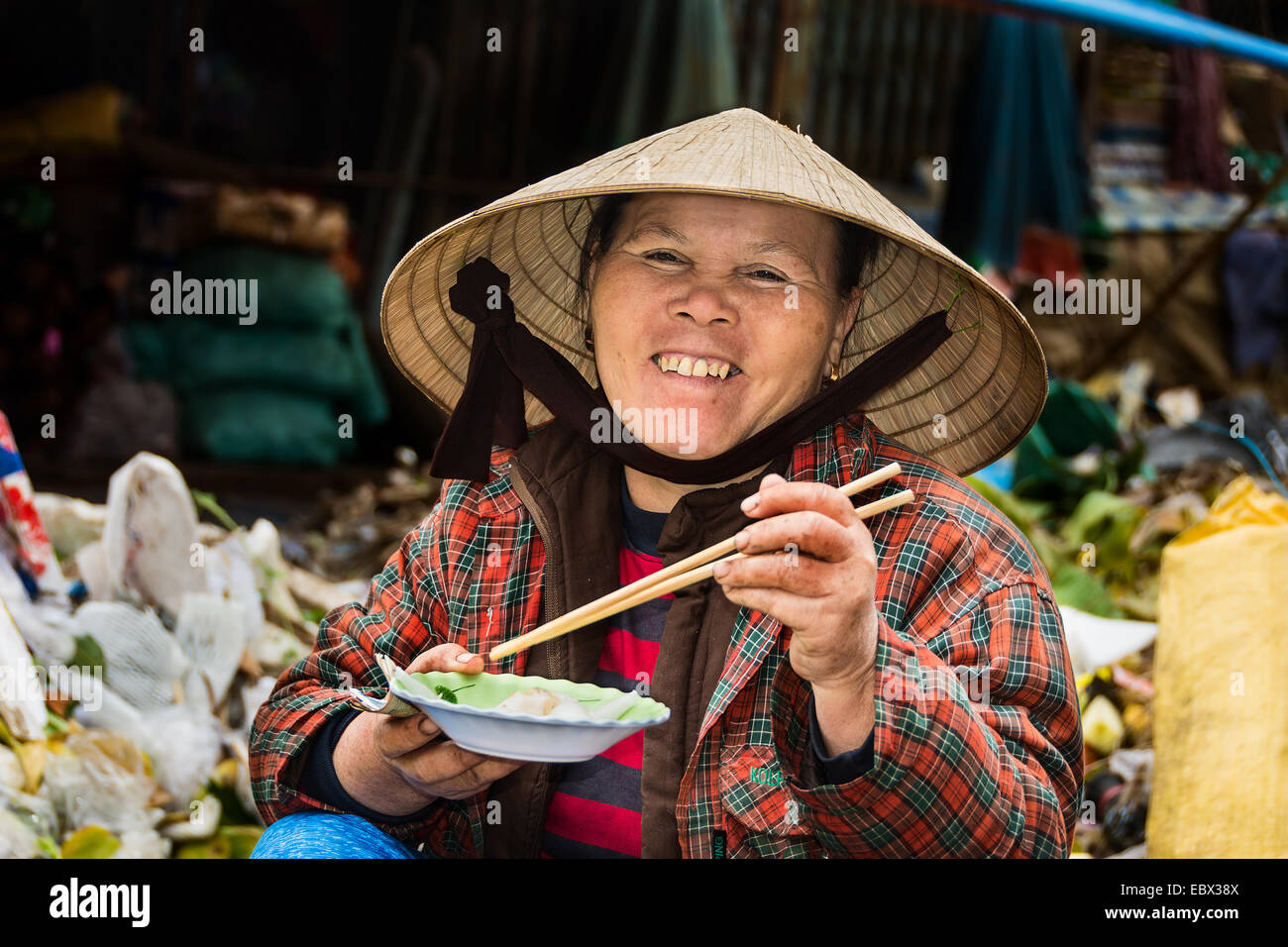 Vietnamese lady smiling at the camera eating her lunch. - Stock Image