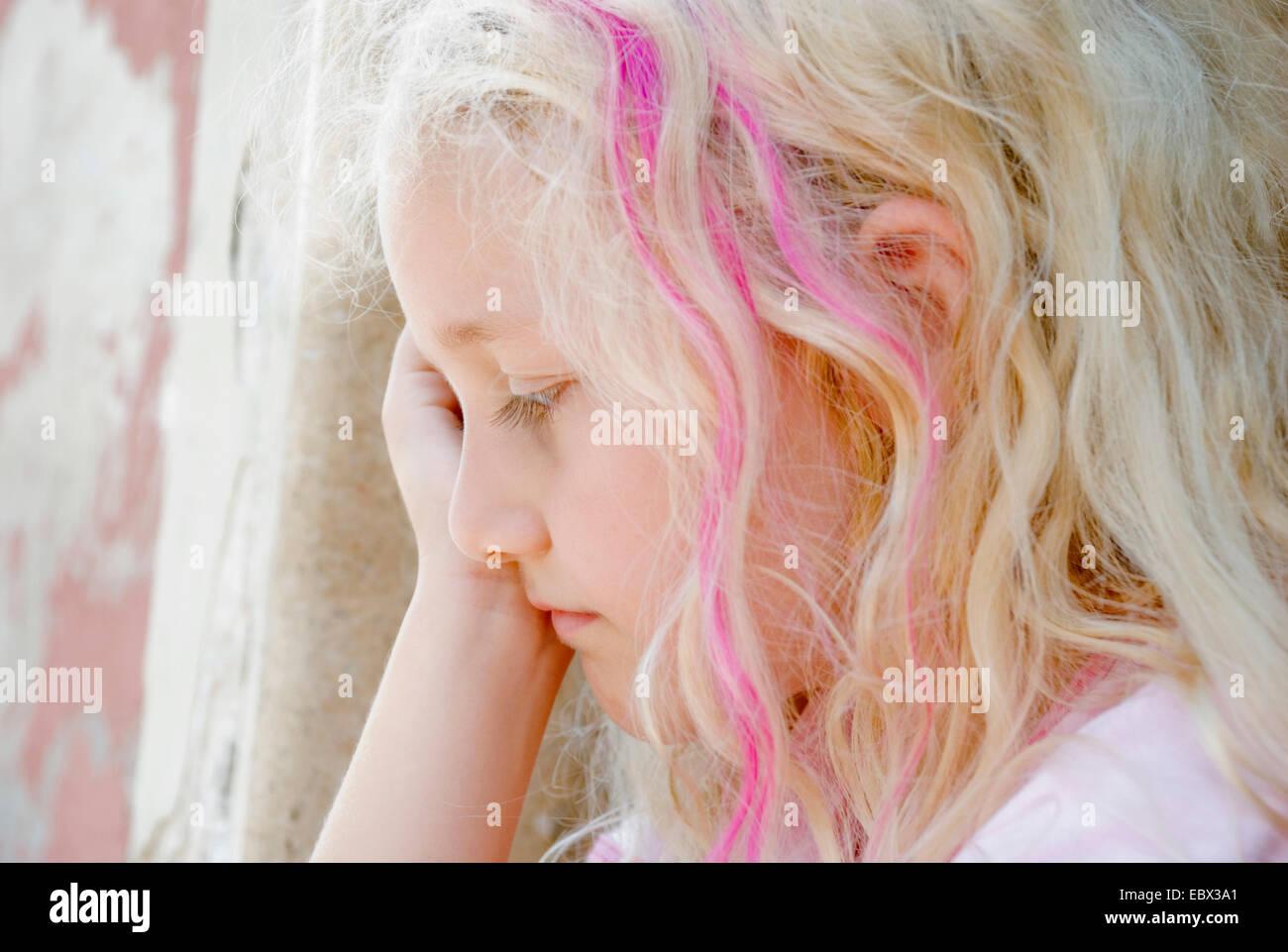 sad girl crouching at a wall - Stock Image