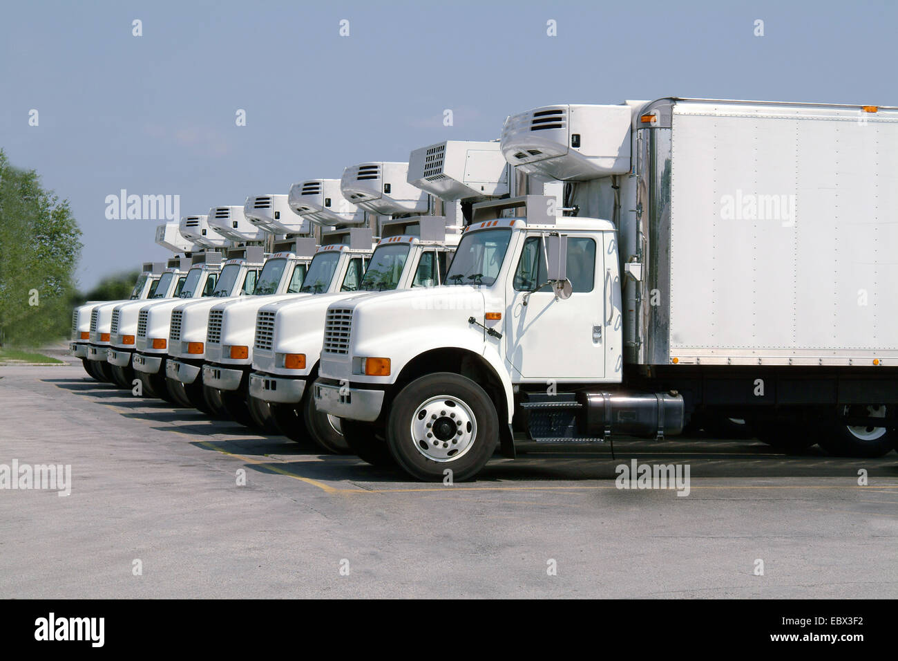 eight idenentical trucks standing in a row side by side - Stock Image