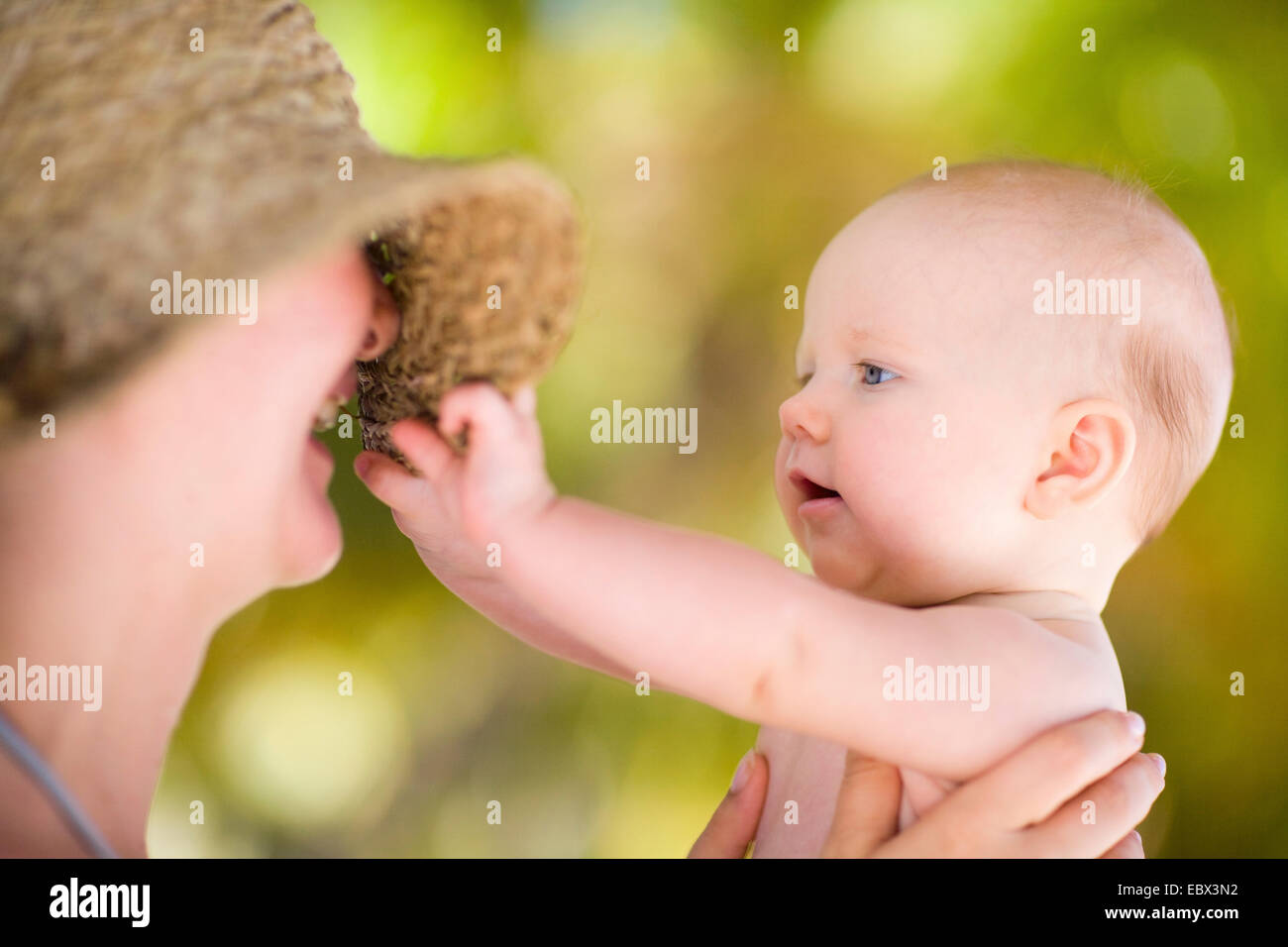 Mother and baby daughter outdoors at summer day - Stock Image