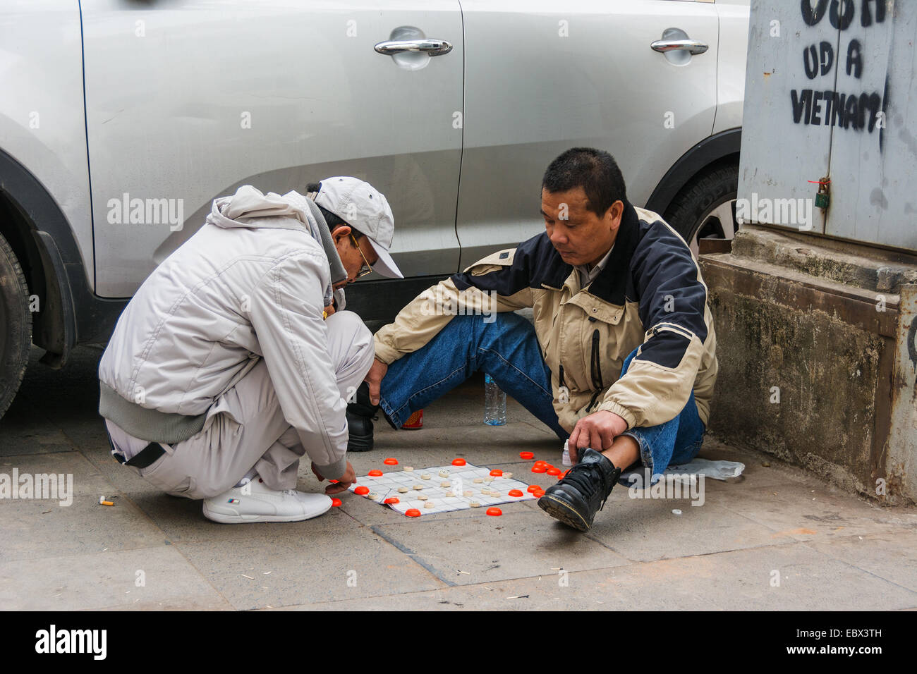 Two Vietnamese men playing checkers in the street in Hanoi Stock Photo