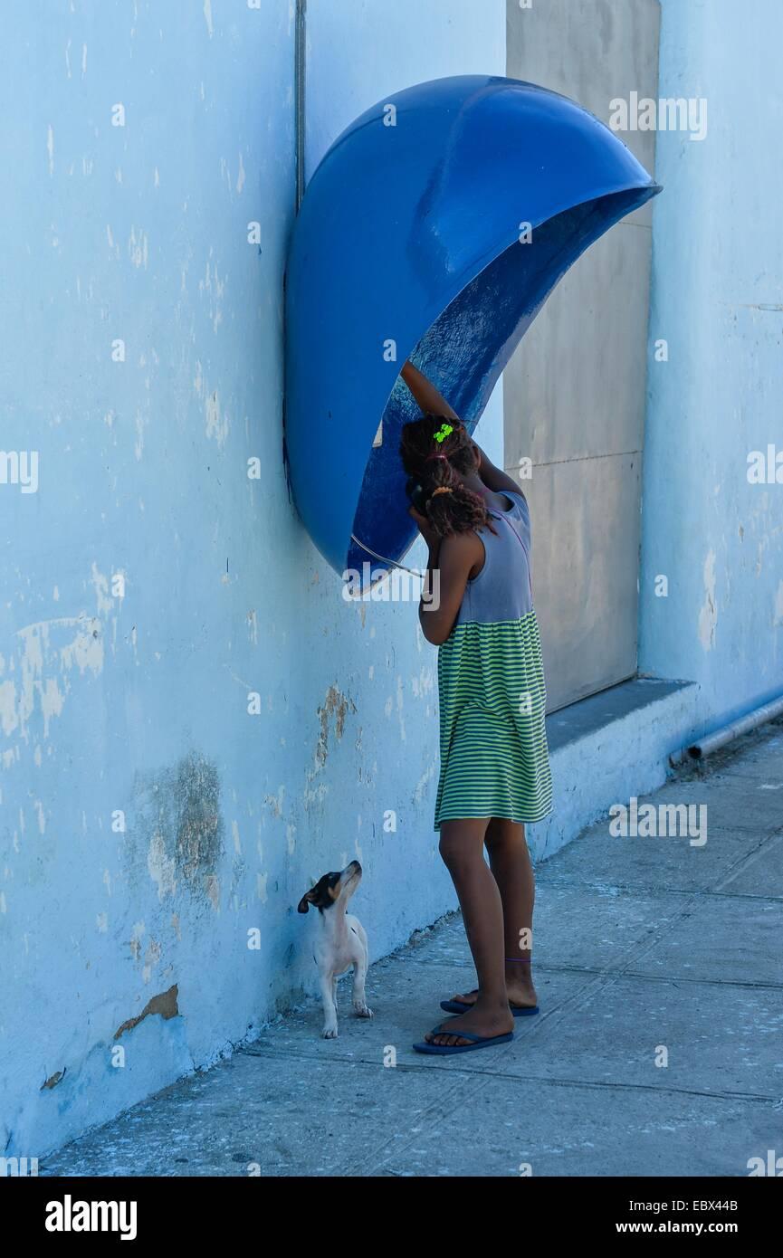A Cuban girl using a telephone kiosk in Cienfuegos Cuba. - Stock Image