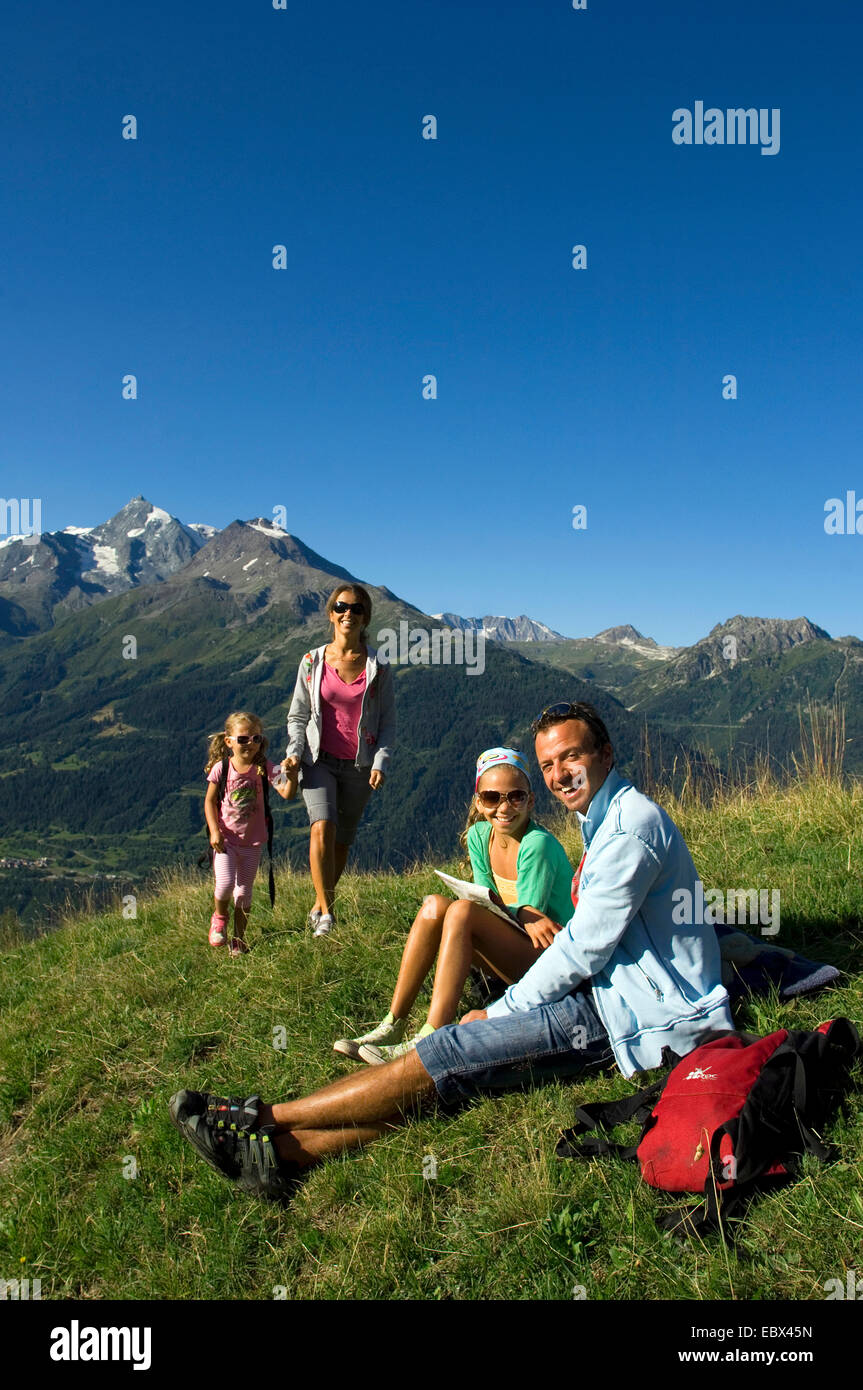 familiy on a mountain trail, girl looking through a field glass, France - Stock Image