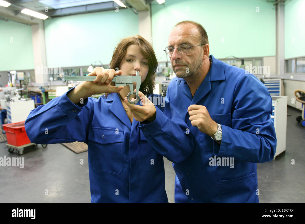 apprentice working with sliding calliper, training supervisor is watching - Stock Image