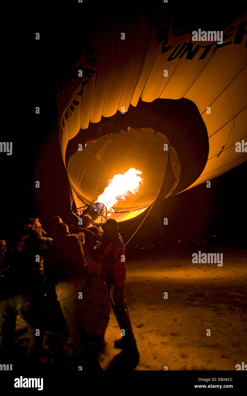 hot-air balloon being held on a snow foeld at night by several persons while being fired and erecting, Germany, - Stock Image
