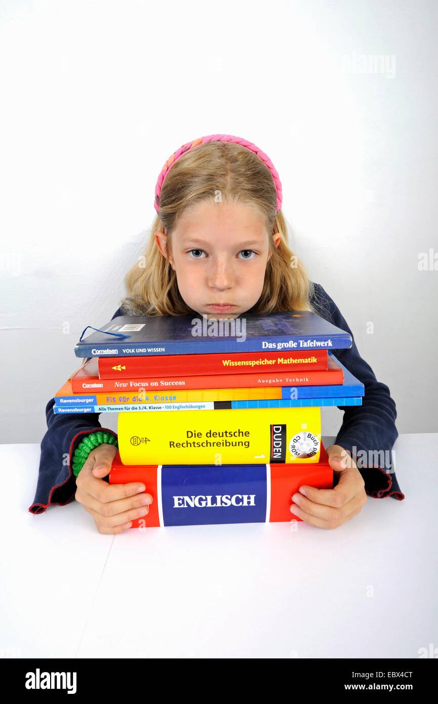 stressed school girl with a stack of school books - Stock Image