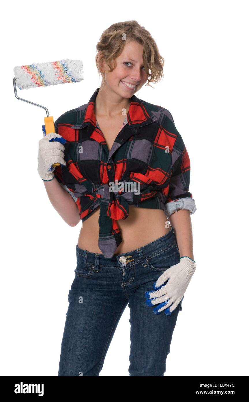 young woman with her knotted shirt baring the belly  is painting walls - Stock Image