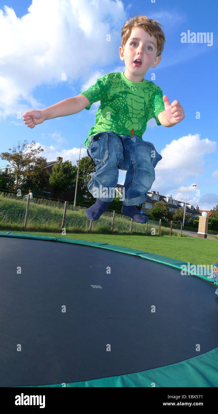 little boy jumping on a trampoline - Stock Image