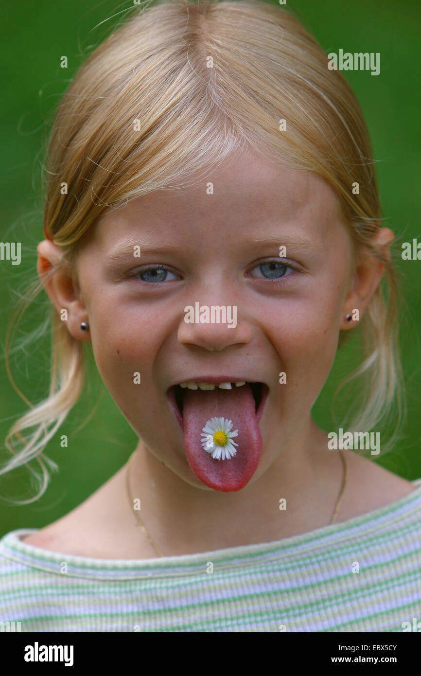common daisy, lawn daisy, English daisy (Bellis perennis), girl with a flower on her tongue, Germany Stock Photo