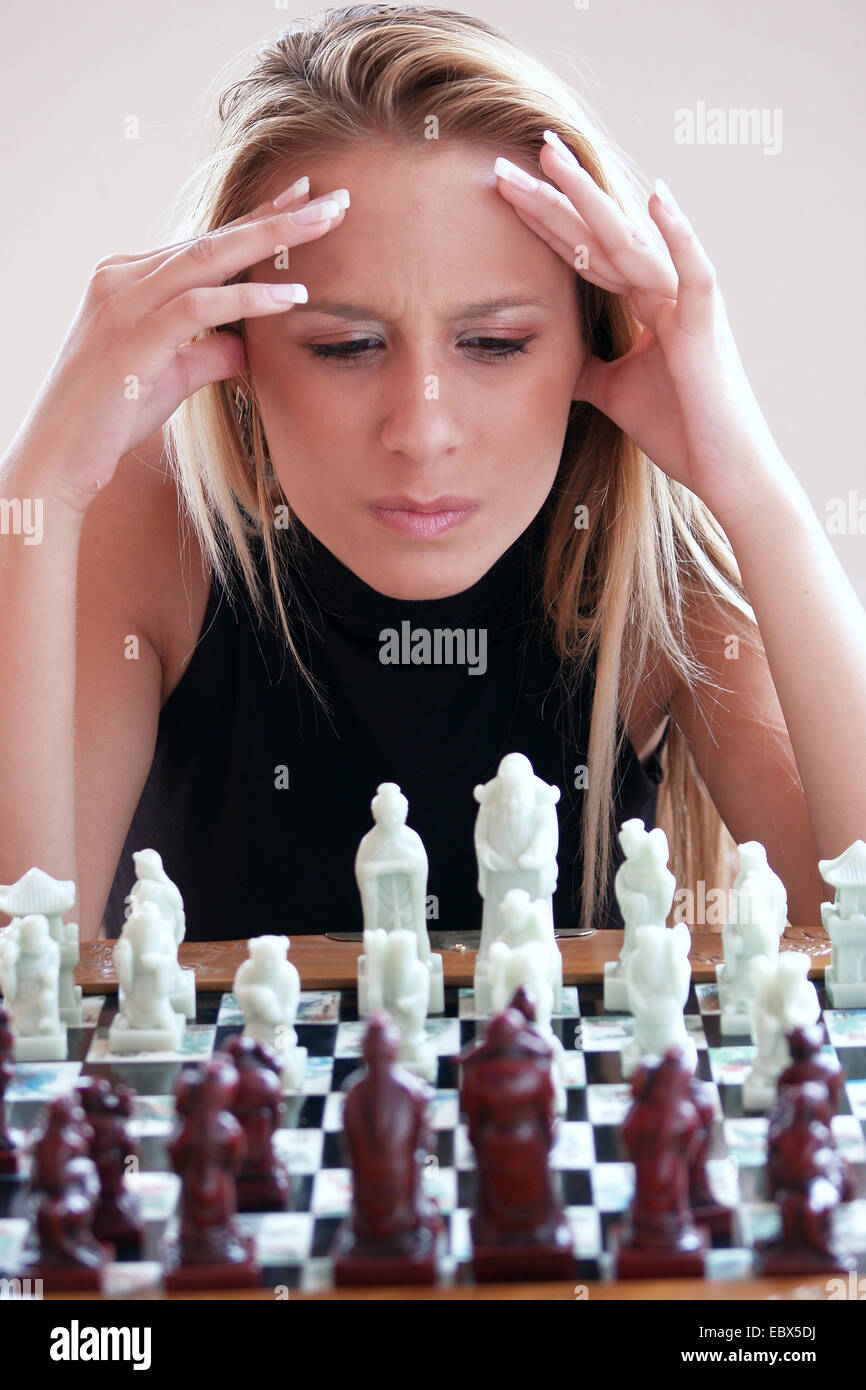 blond young woman sitting in front of a chess board thinking - Stock Image