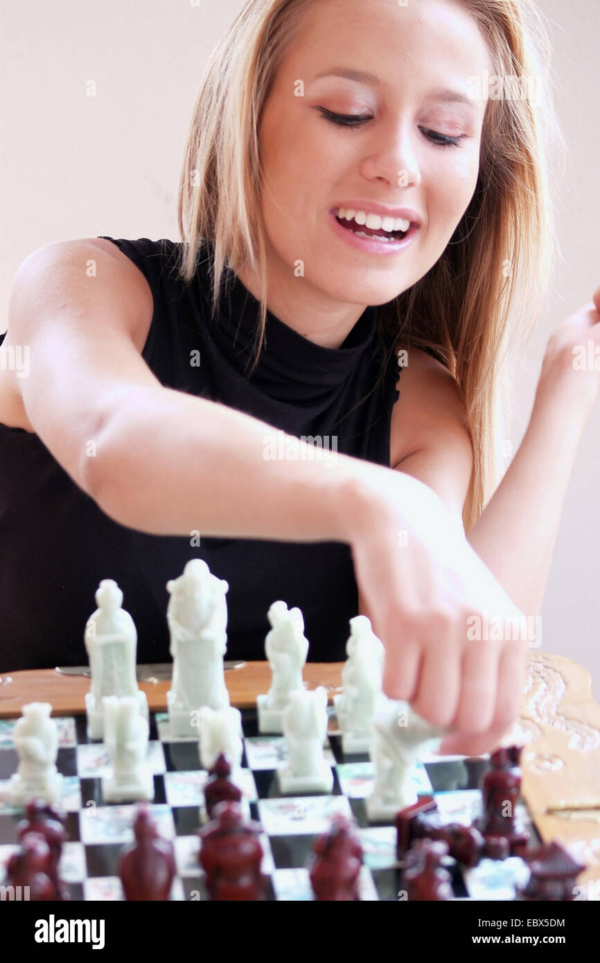 blond young woman sitting in front of a chess board making a move with a smile - Stock Image
