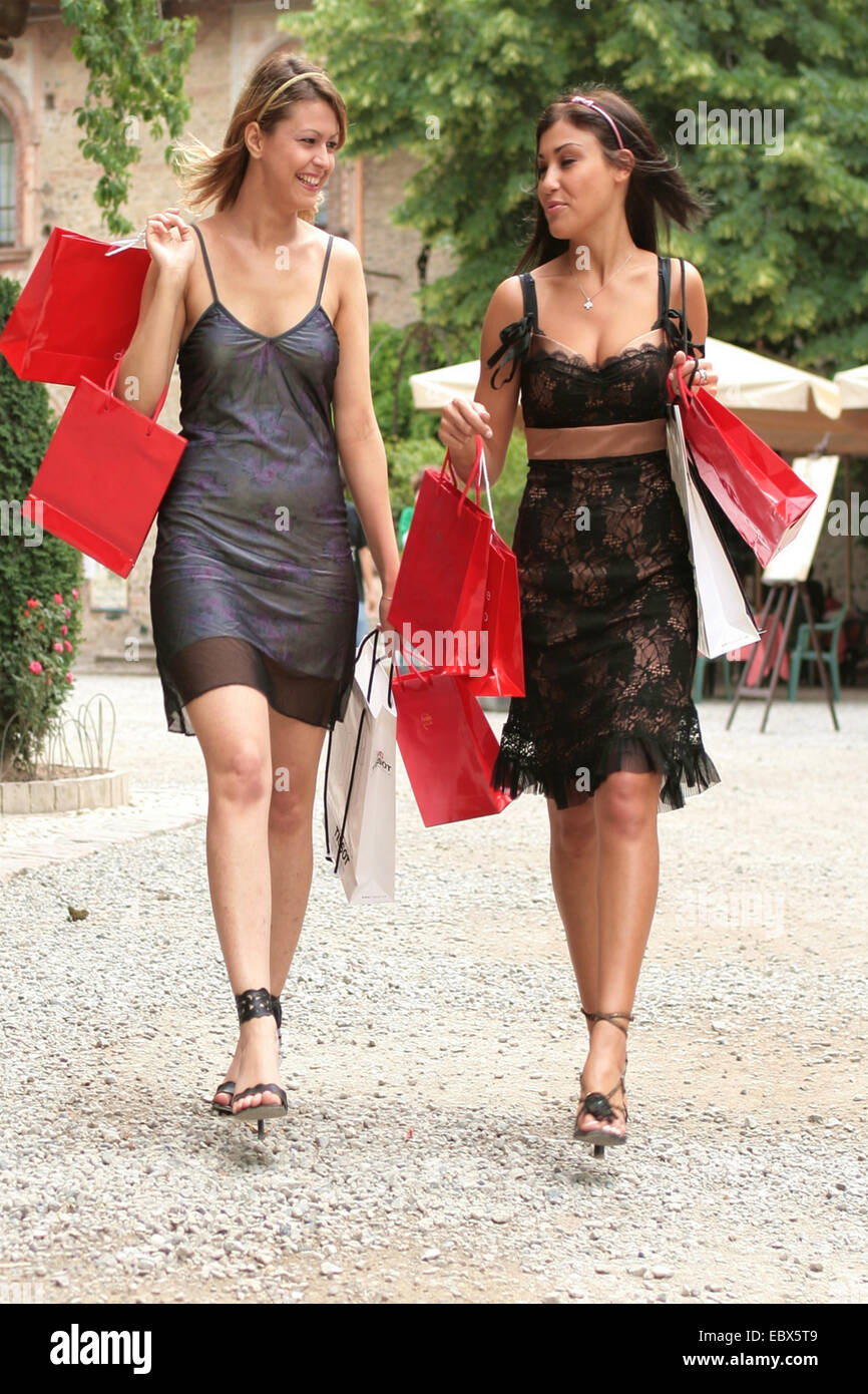 two smiling young women coming back from shopping full of shopping bags - Stock Image