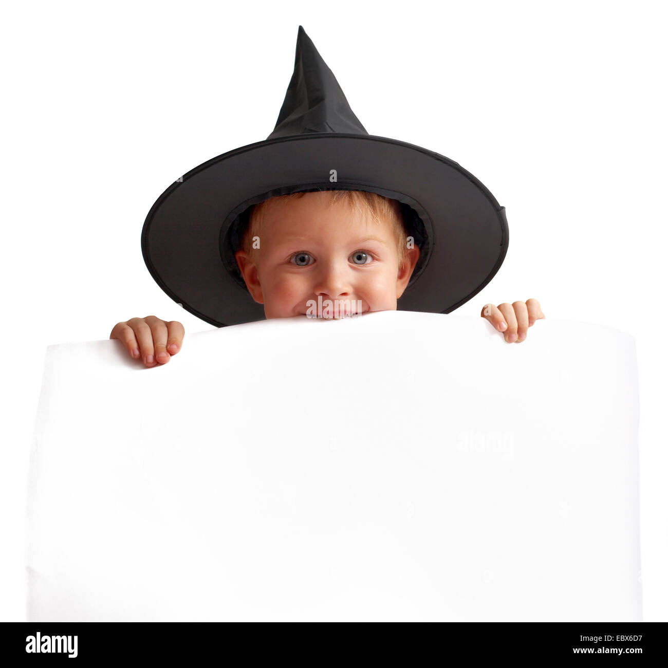 playful boy in witch hat holds white banner. - Stock Image