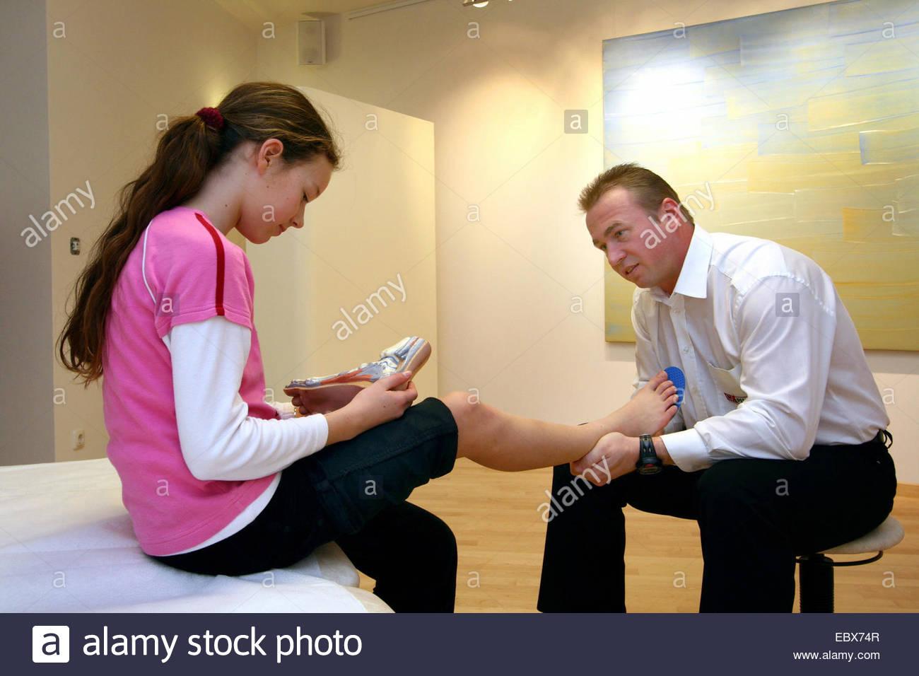 orthopedist adapting the shoe inserts - Stock Image