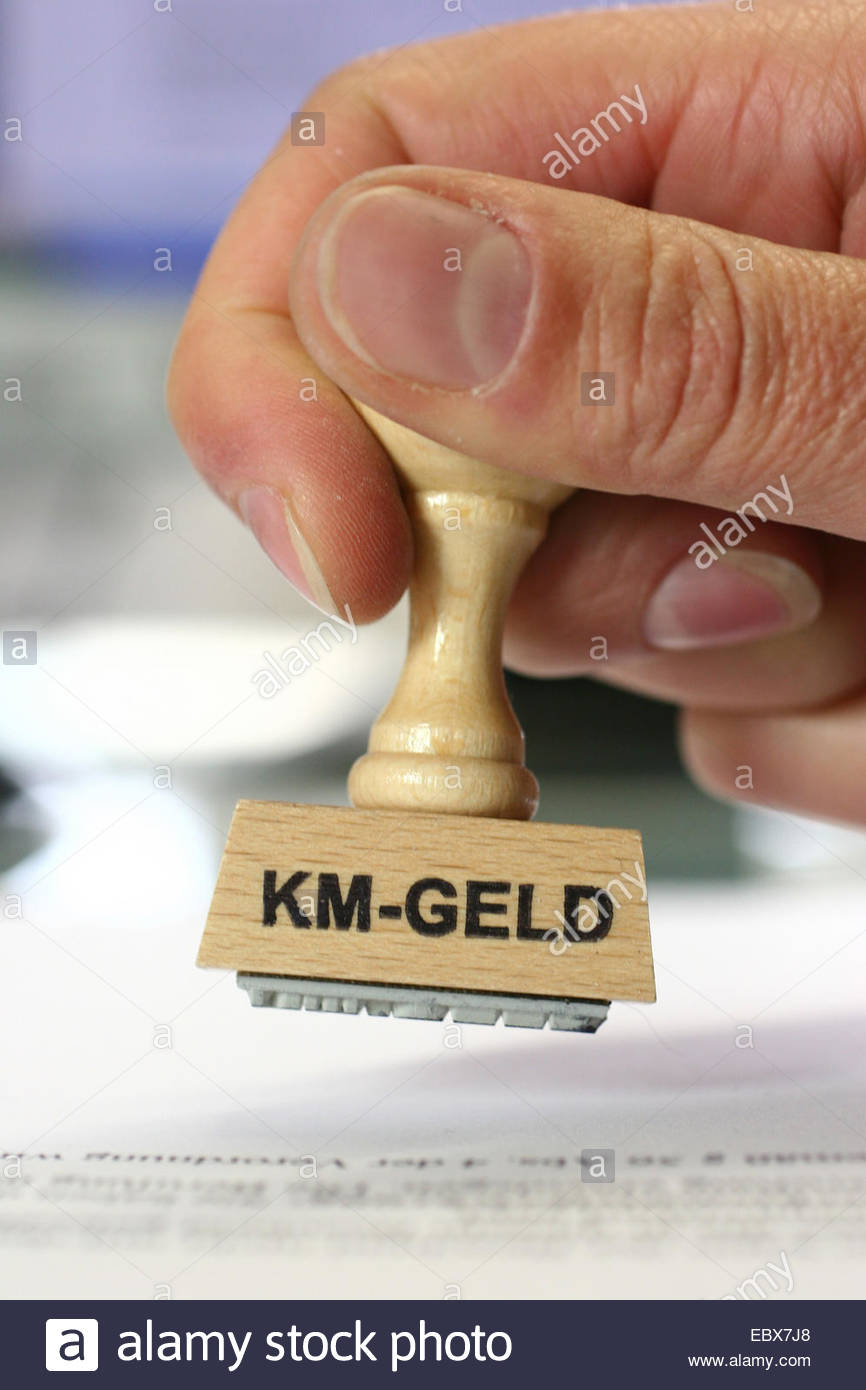 hand with a stamp Km-Geld, mileage - Stock Image