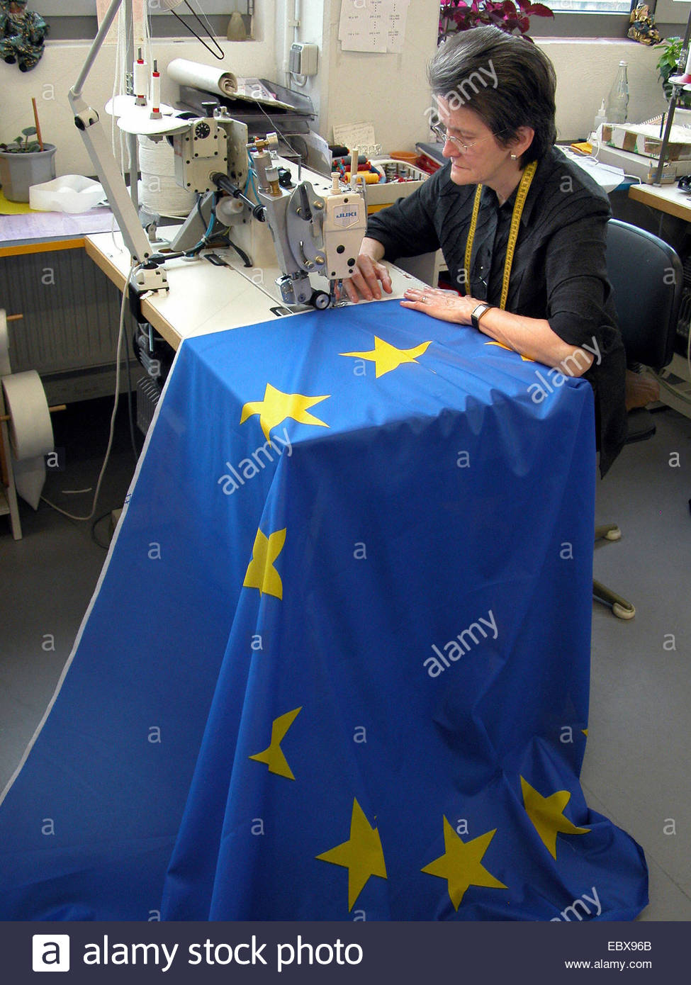 Woman sews European Union flag - Stock Image