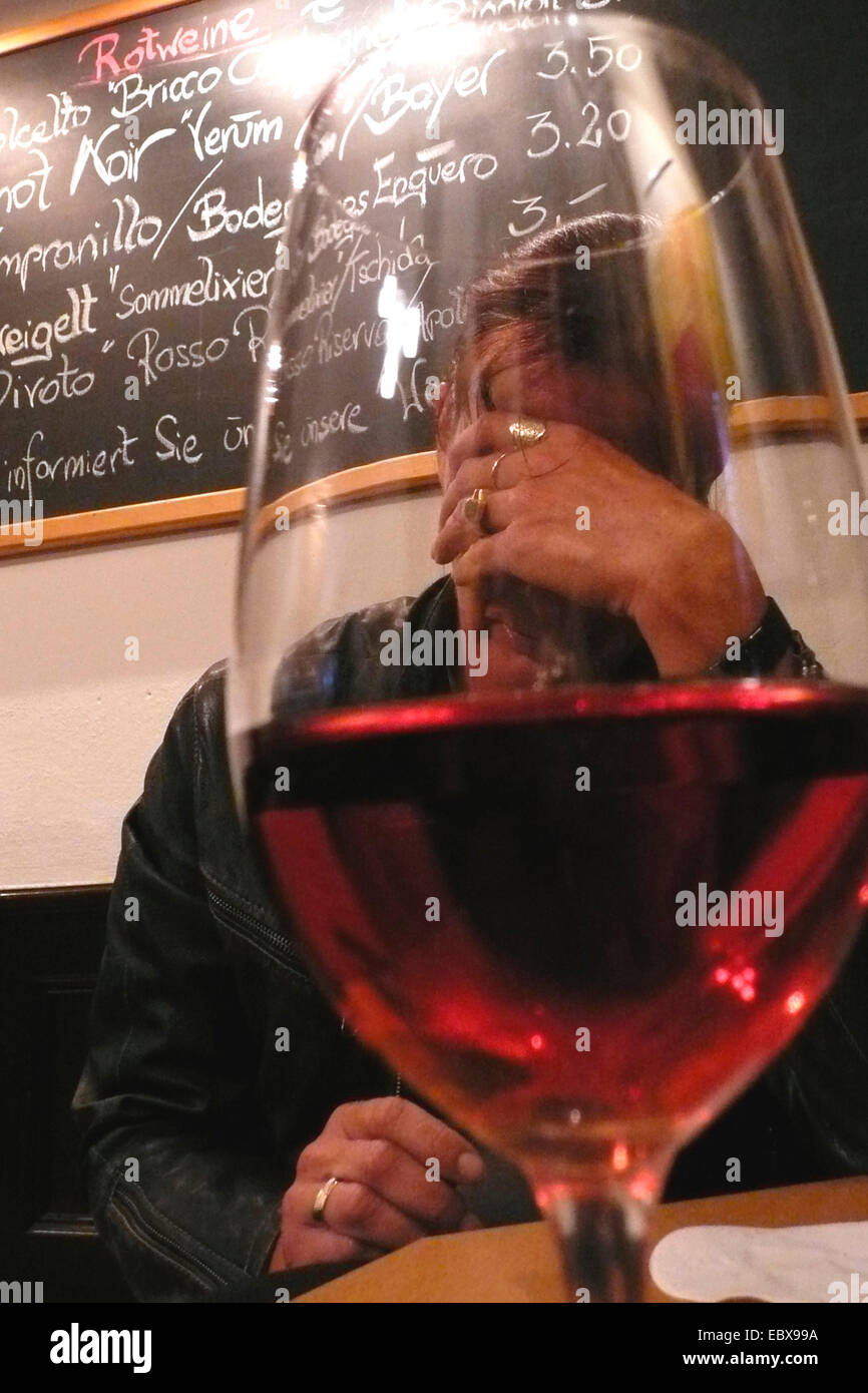 man sitting desperated behind half ful red wine glass - Stock Image