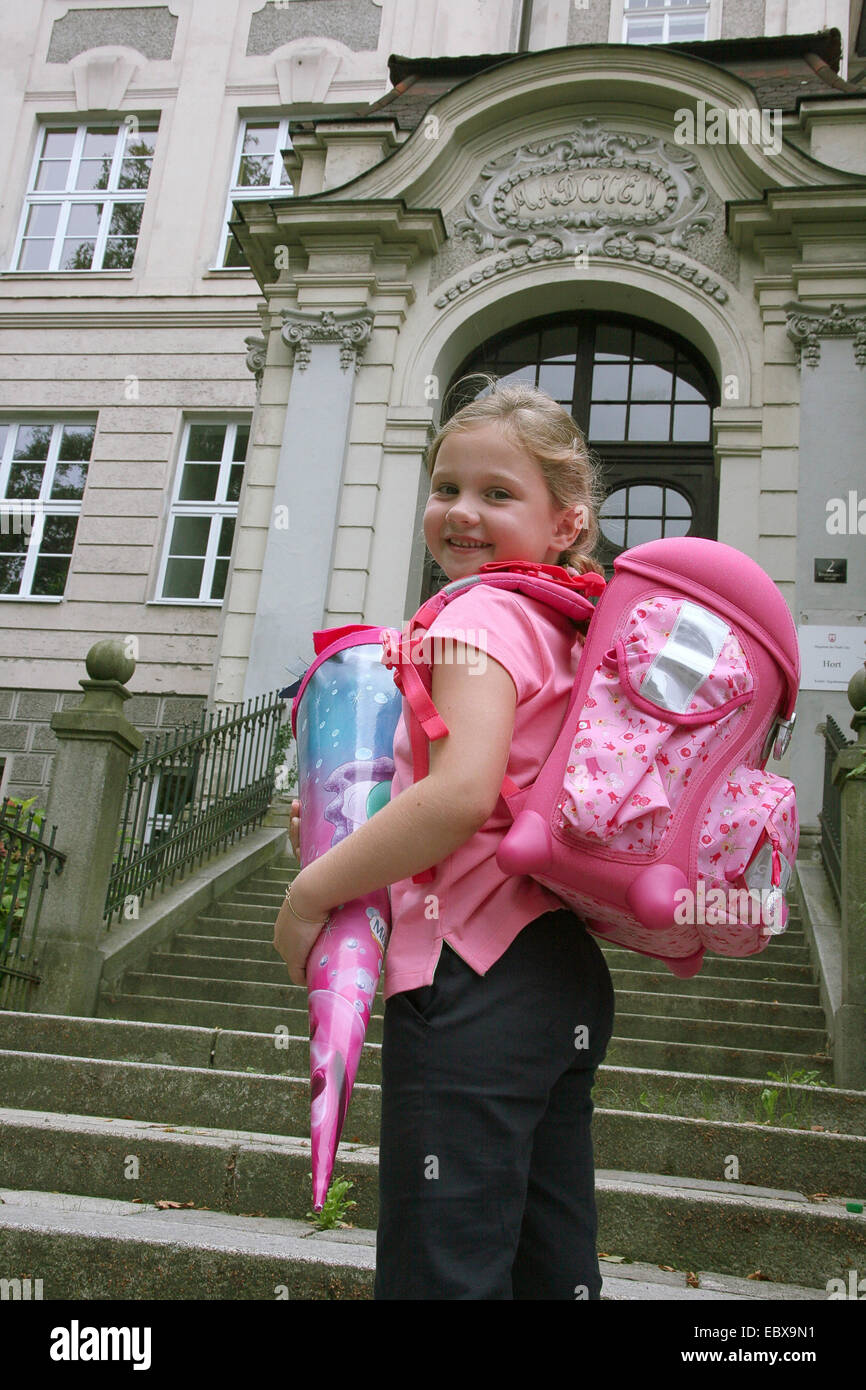 First-grader with a miscounsel satchel and a school-cornet stands in front of a girl`s school - Stock Image