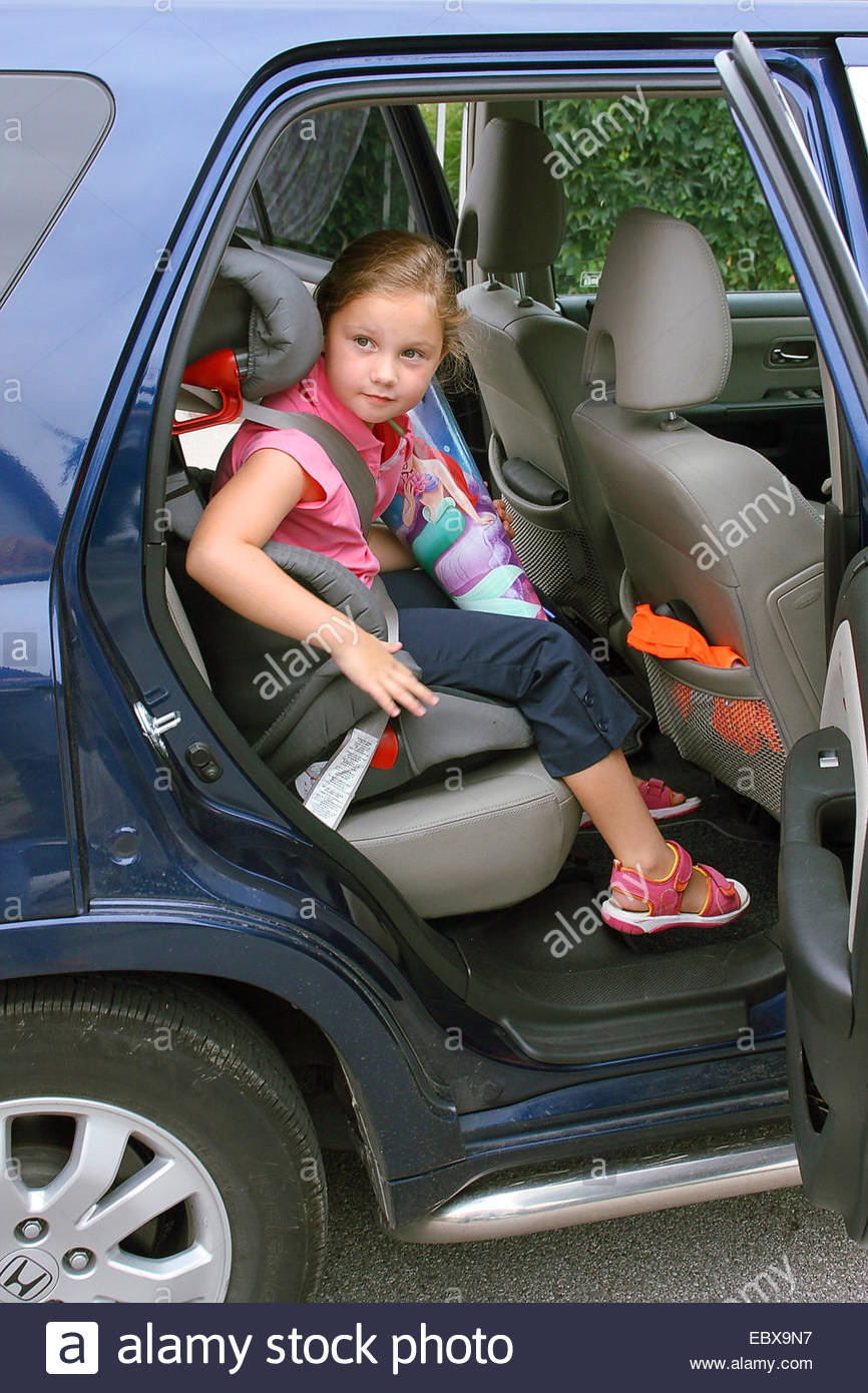 First-grader sits in a child seat - Stock Image