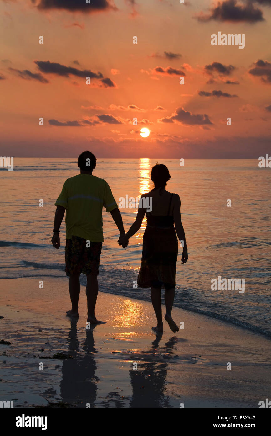 couple walking barefooted along the beach at sunset - Stock Image