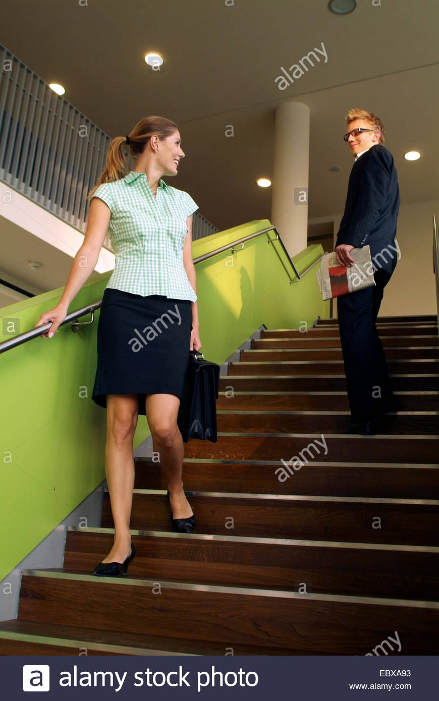 man coming across a woman on stairs - Stock Image