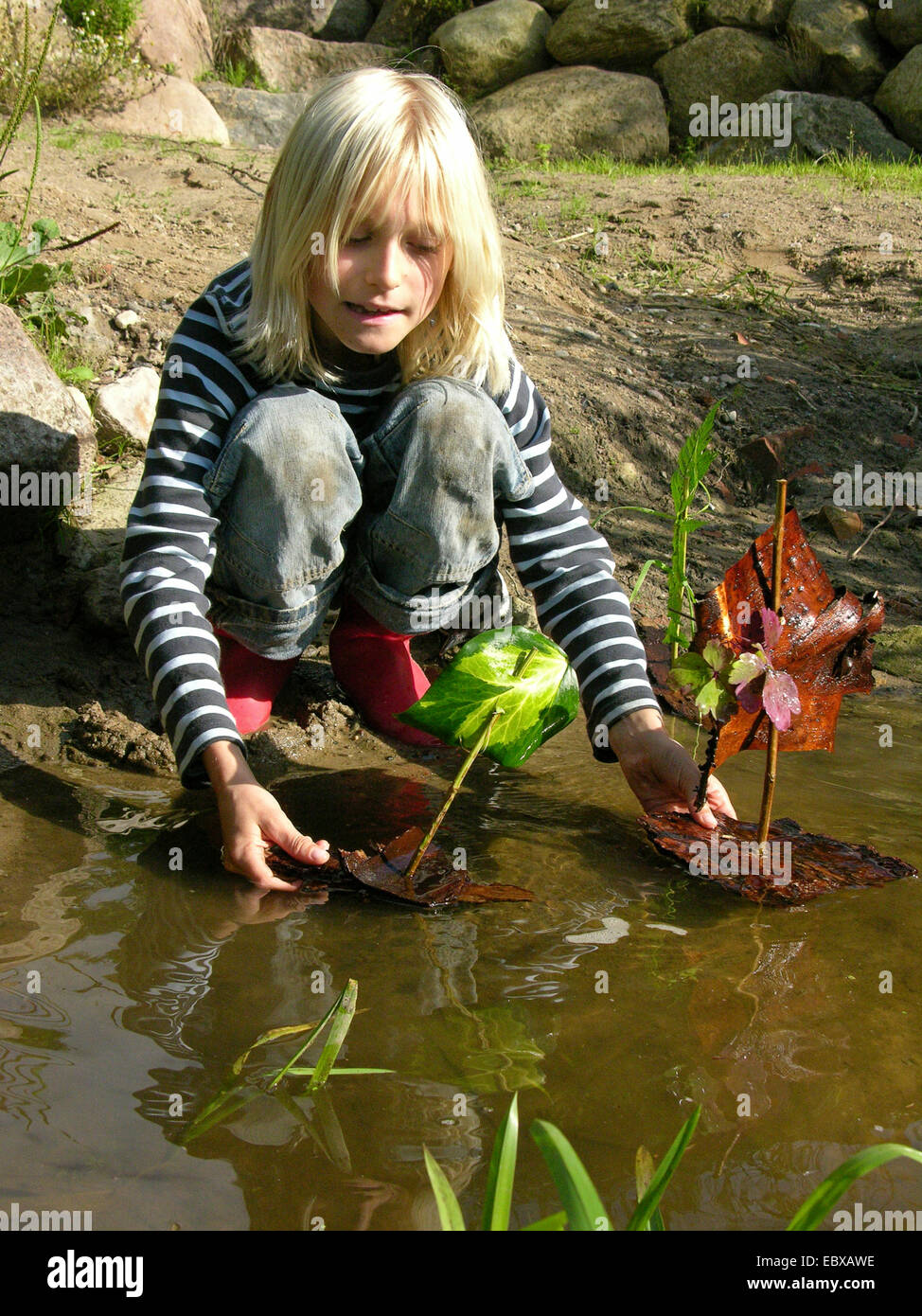 child at a creek putting two bark ships in the water - Stock Image